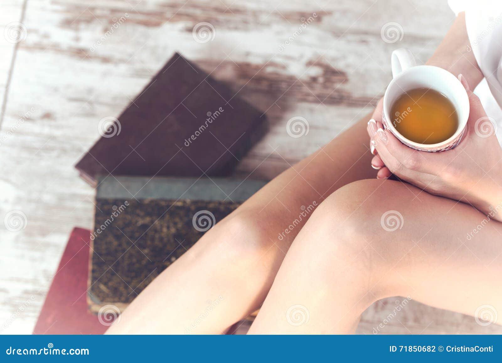 Donna che beve una tazza di tè nel rilassamento