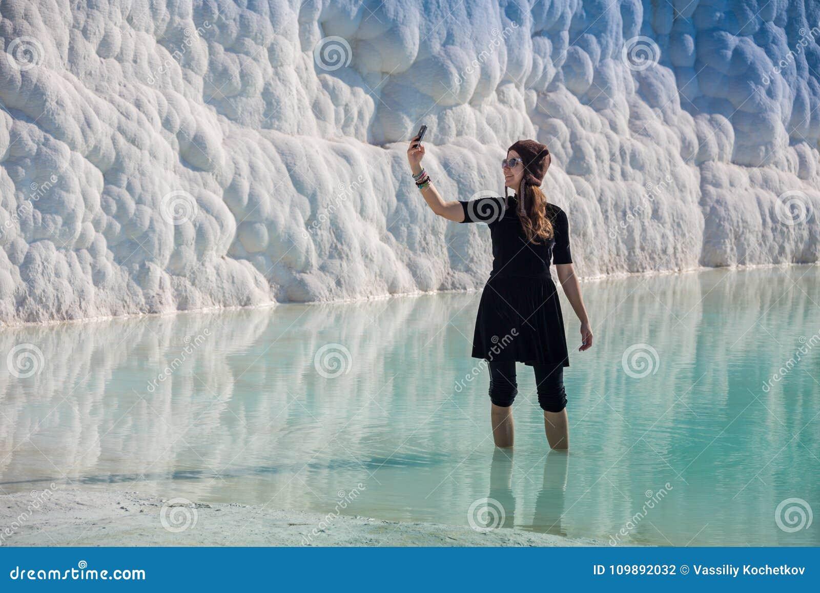 Donna che cammina sui terrazzi a Pamukkale Castello del cotone nel turco ed è sito naturale