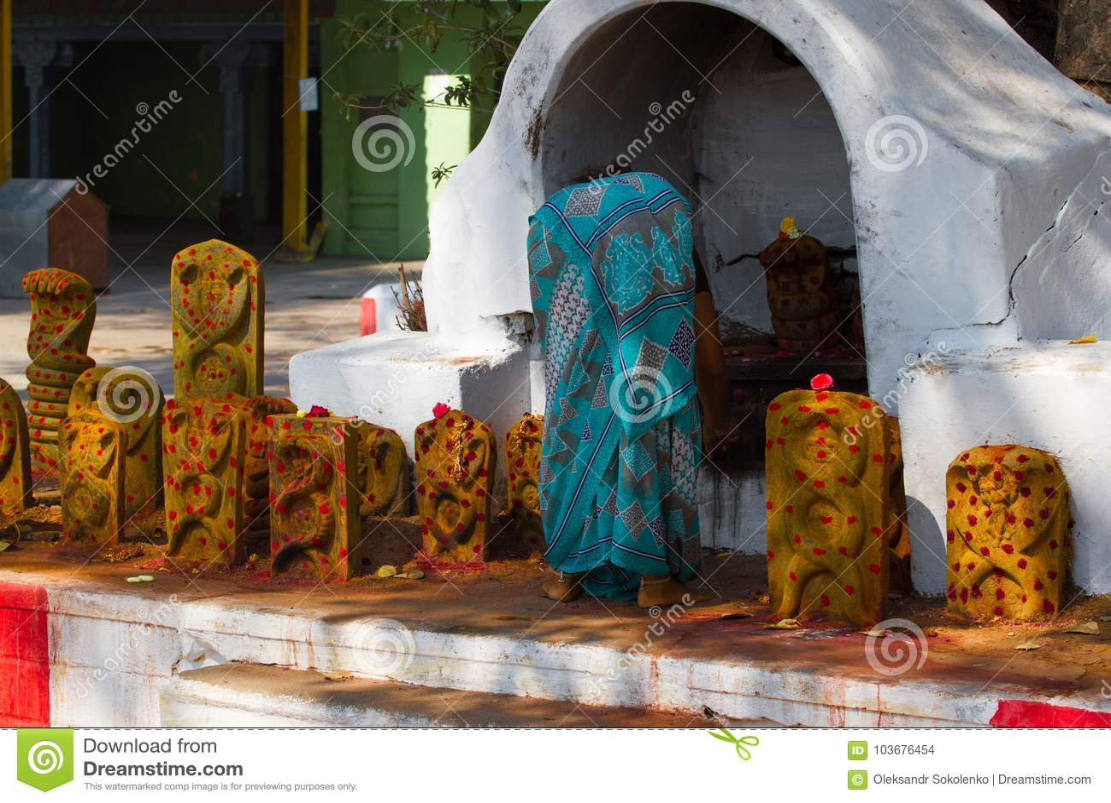 Donna che commemora i morti nel tempio Gruppo di monumenti gialli con i punti rossi in tempio di Shiva, Tamil Nadu, India
