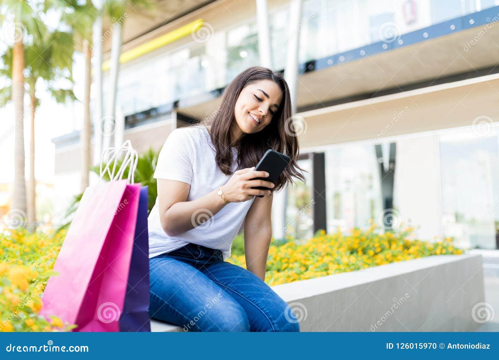 Donna che controlla i messaggi sul telefono cellulare dai sacchetti della spesa