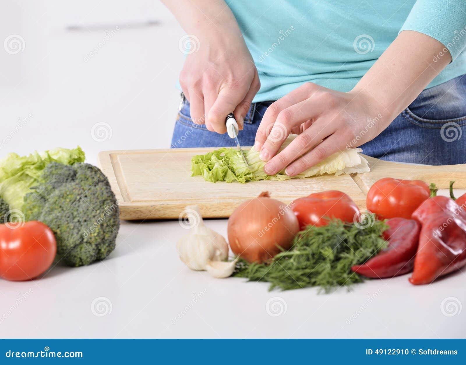 Donna che cucina nella nuova cucina che produce alimento sano con le verdure