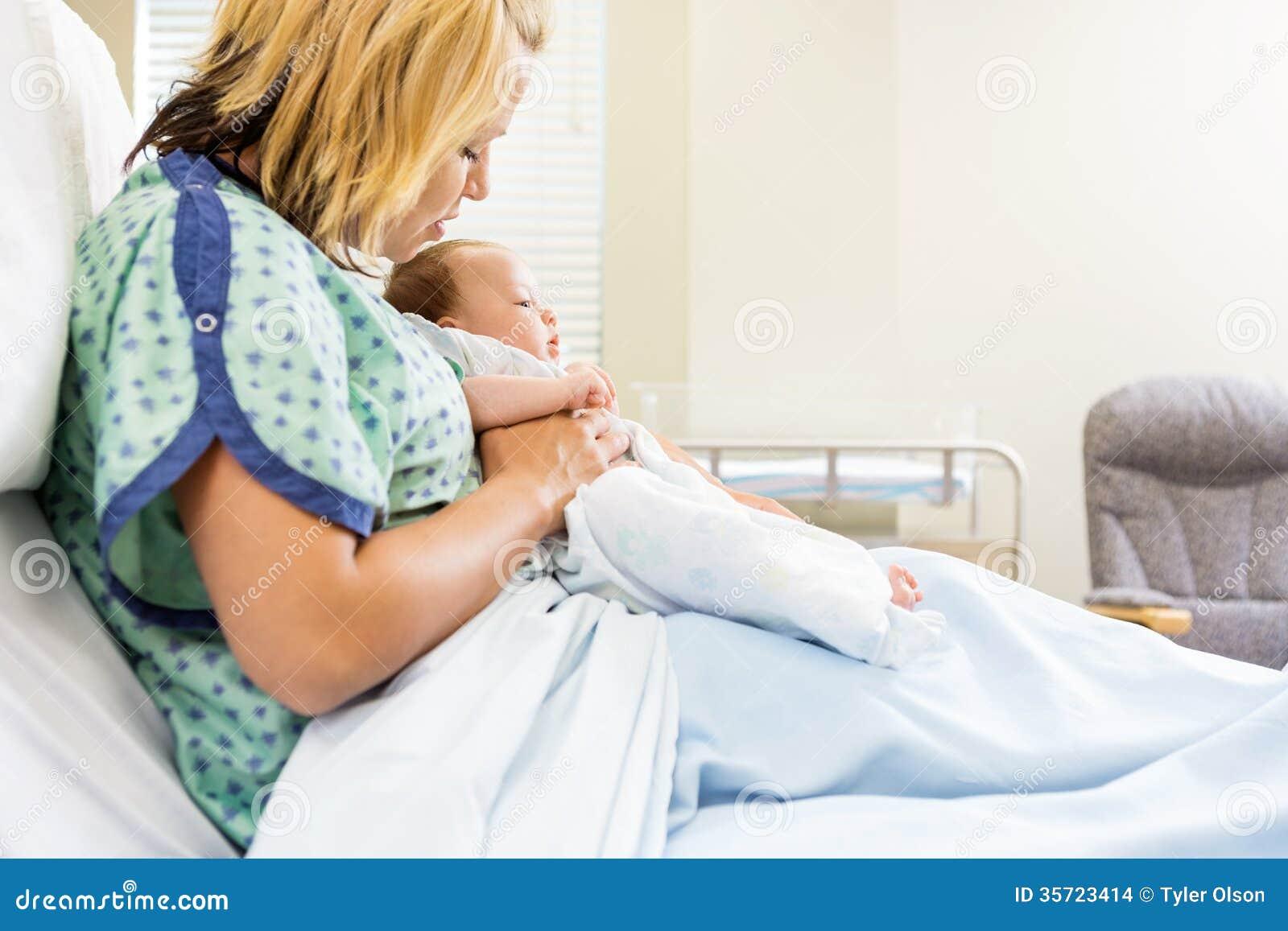 Donna che esamina Babygirl neonato sul letto di ospedale