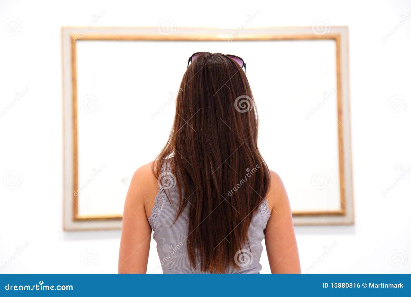 Donna che esamina la pittura di arte nel museo