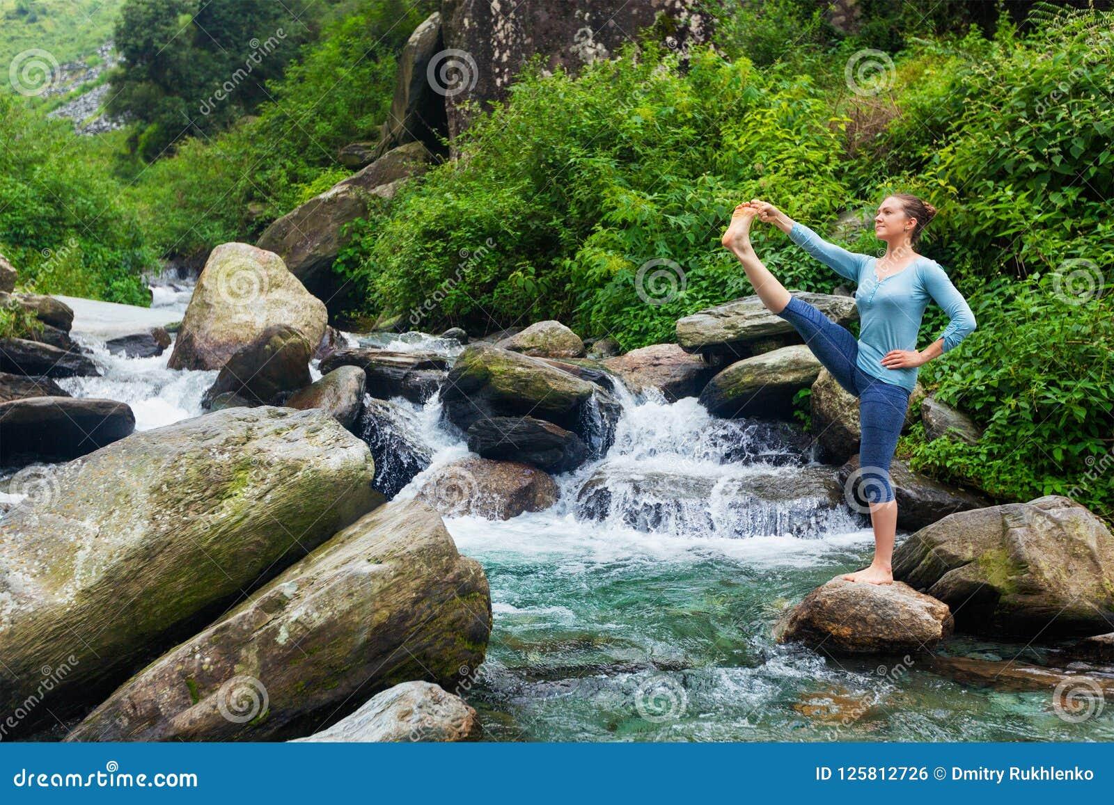 Donna che fa asana di yoga di Ashtanga Vinyasa all aperto alla cascata