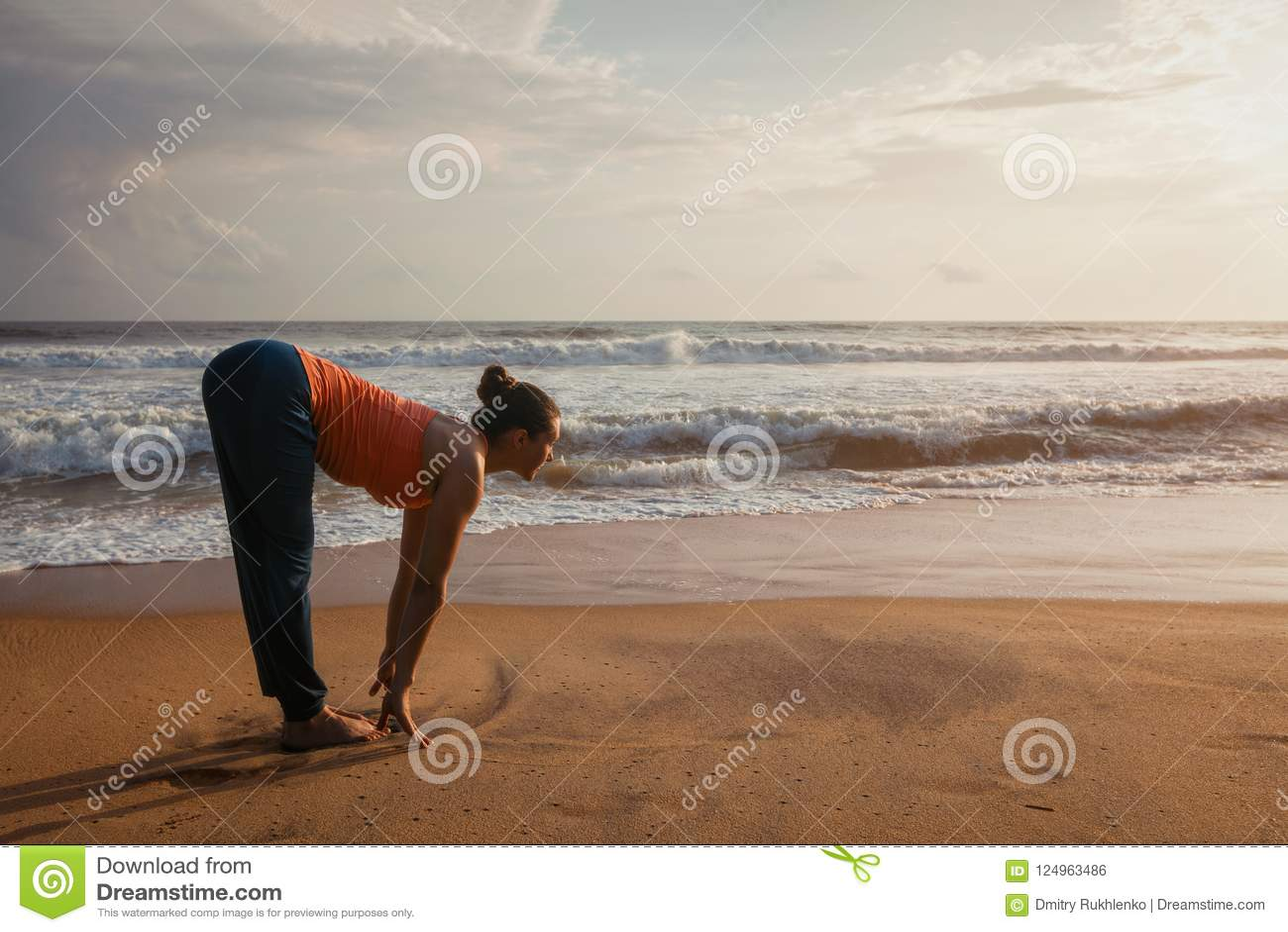 Donna che fa saluto Surya Namaskar di Sun di yoga sulla spiaggia
