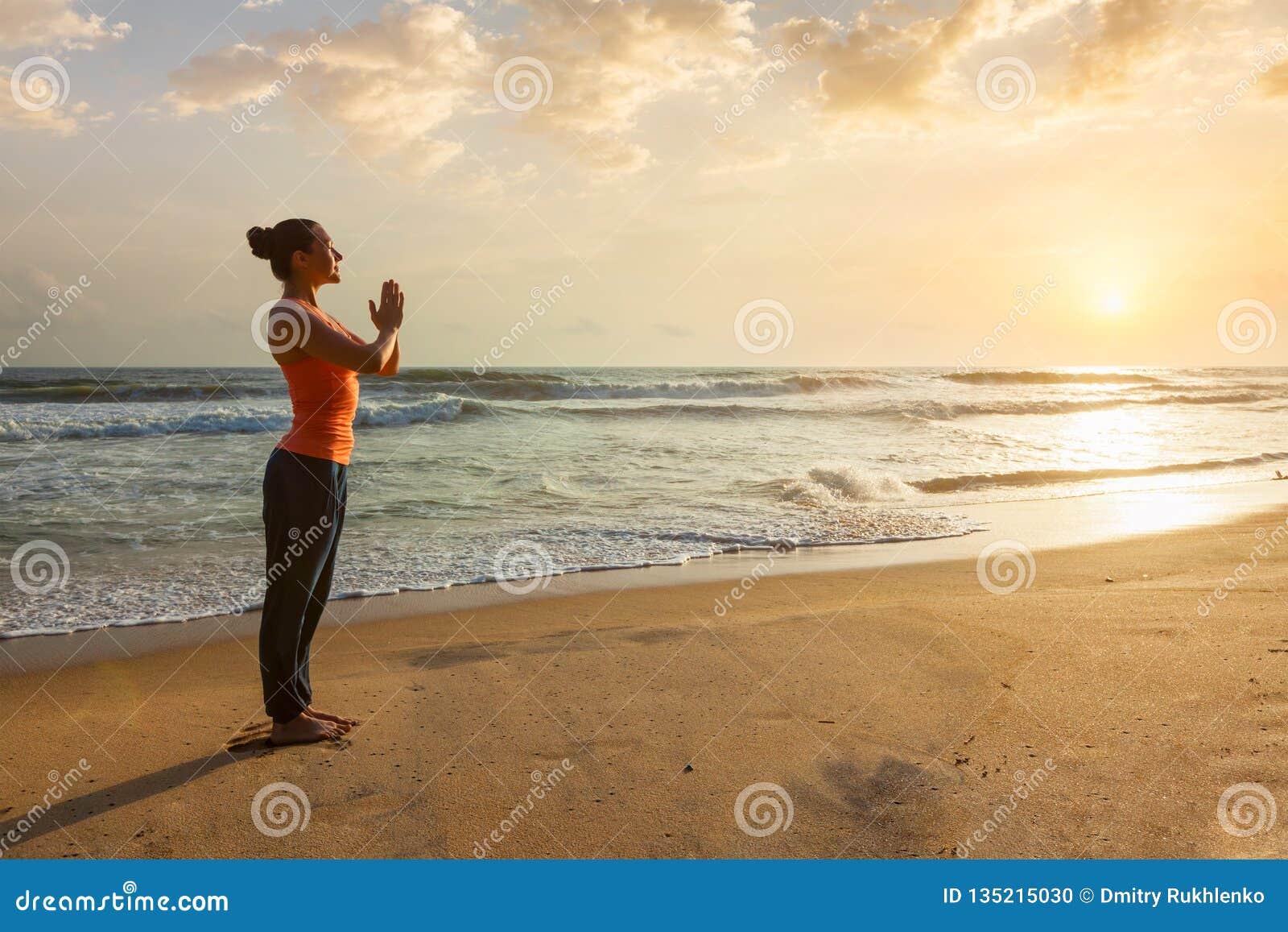 Donna che fa yoga sulla spiaggia