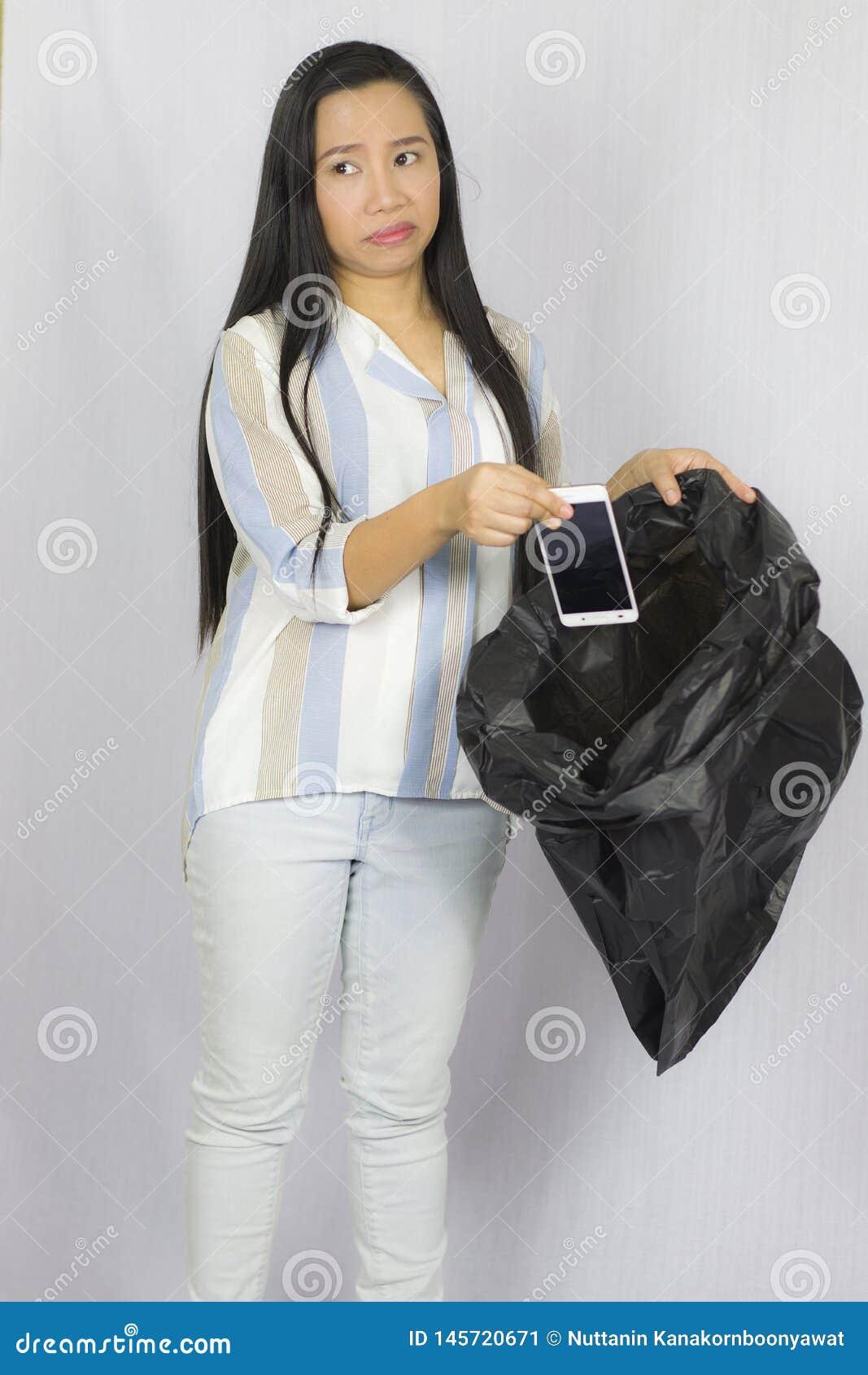 Donna che getta il suo telefono nella borsa di immondizia, posare isolata su fondo grigio
