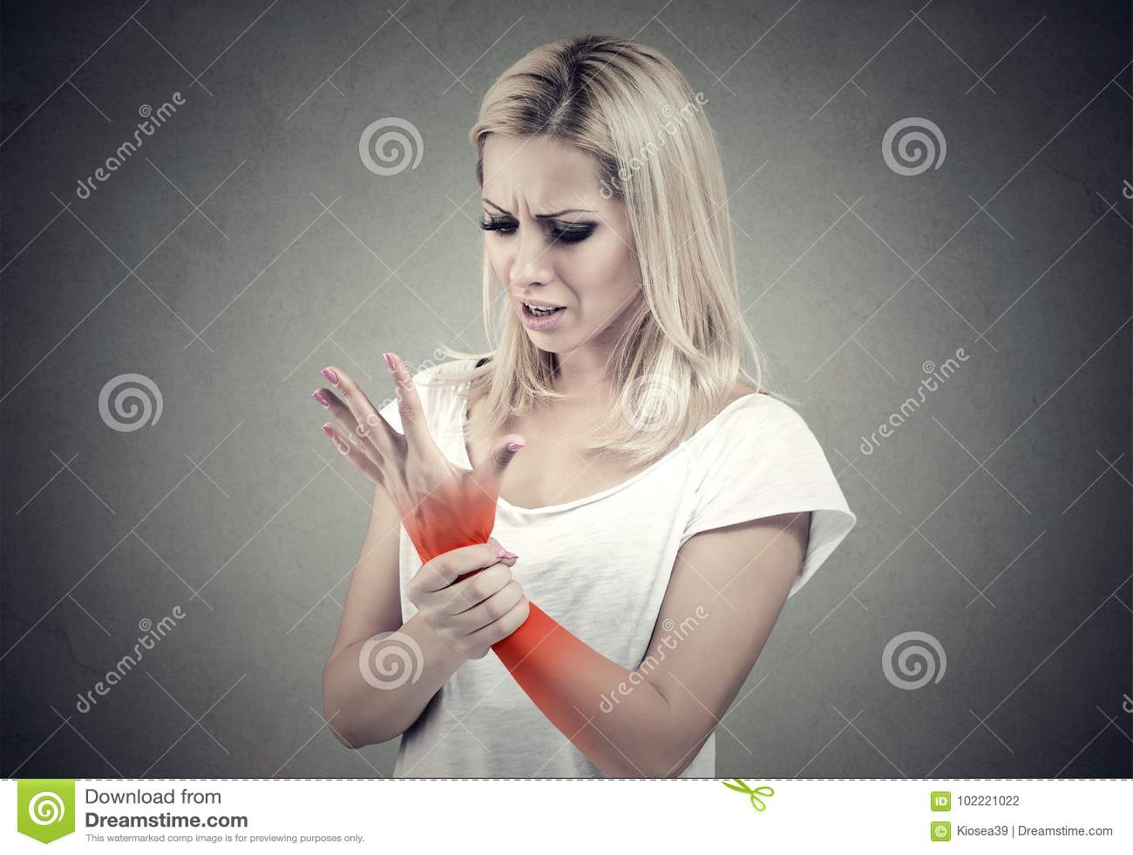 Donna che giudica la sua posizione dolorosa di dolore di distorsione del polso indicata dal punto rosso