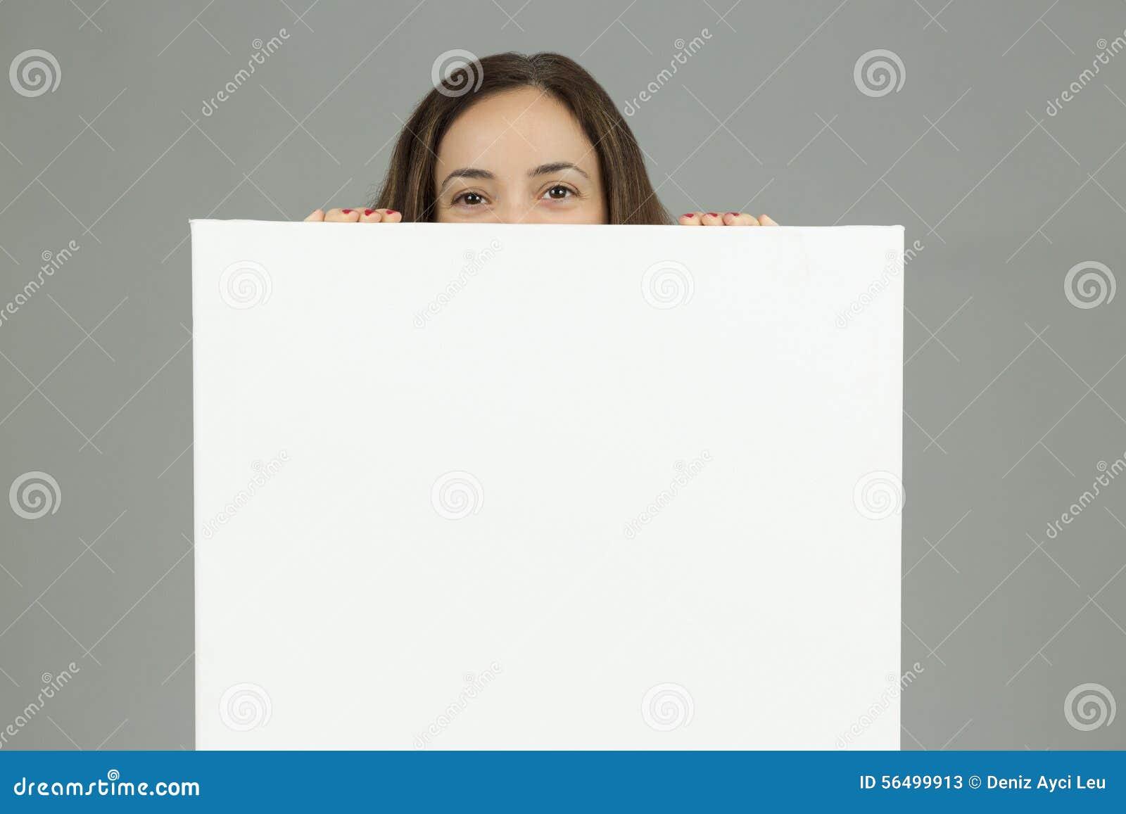 Donna che guarda da dietro un bordo di pubblicità in bianco