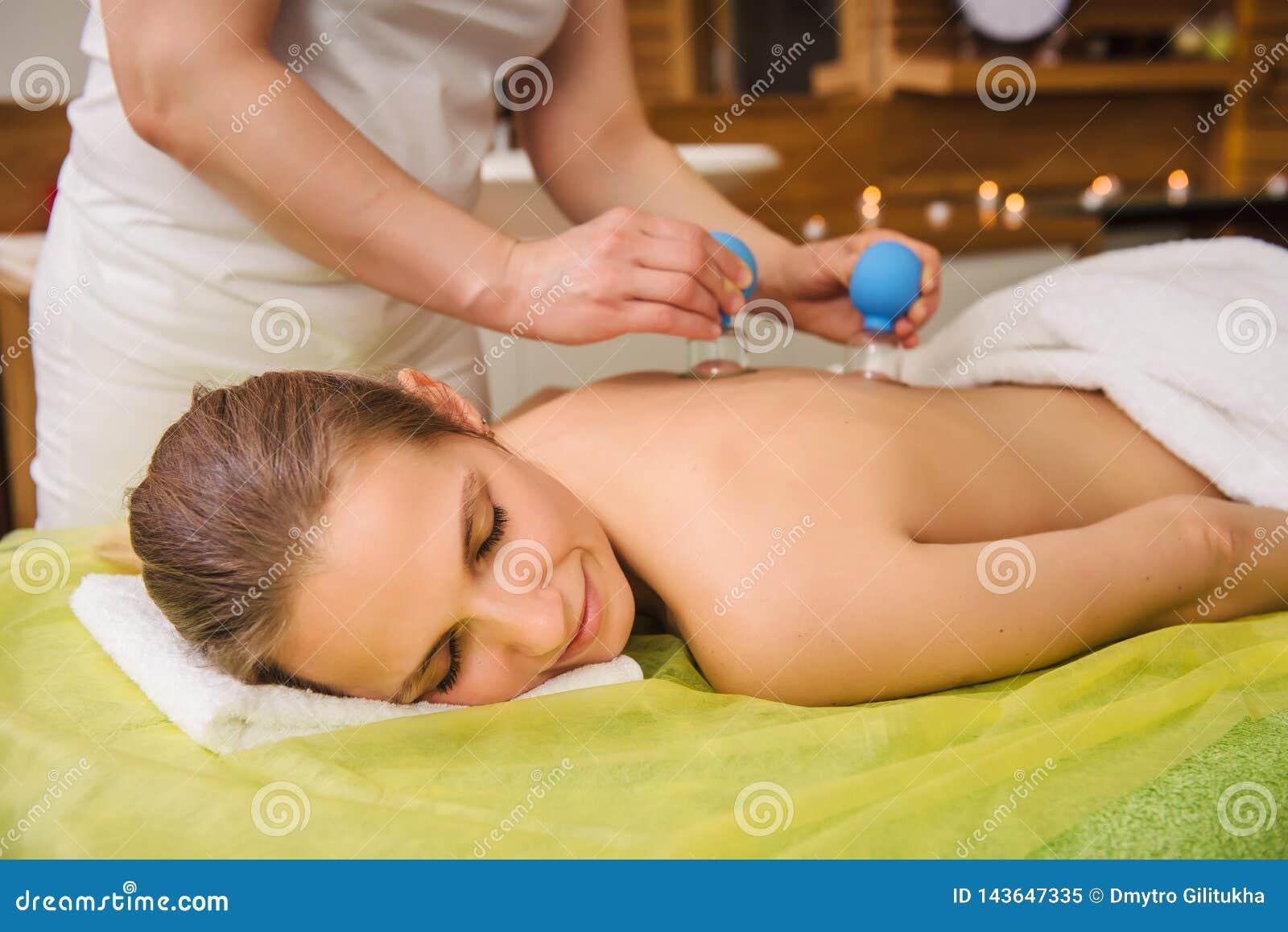 Donna che ha massaggio foggiante a coppa di vuoto caldo del barattolo nel centro della stazione termale