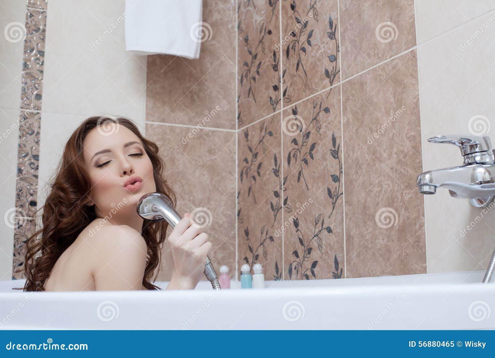 Donna che imbroglia intorno mentre cantando nel bagno