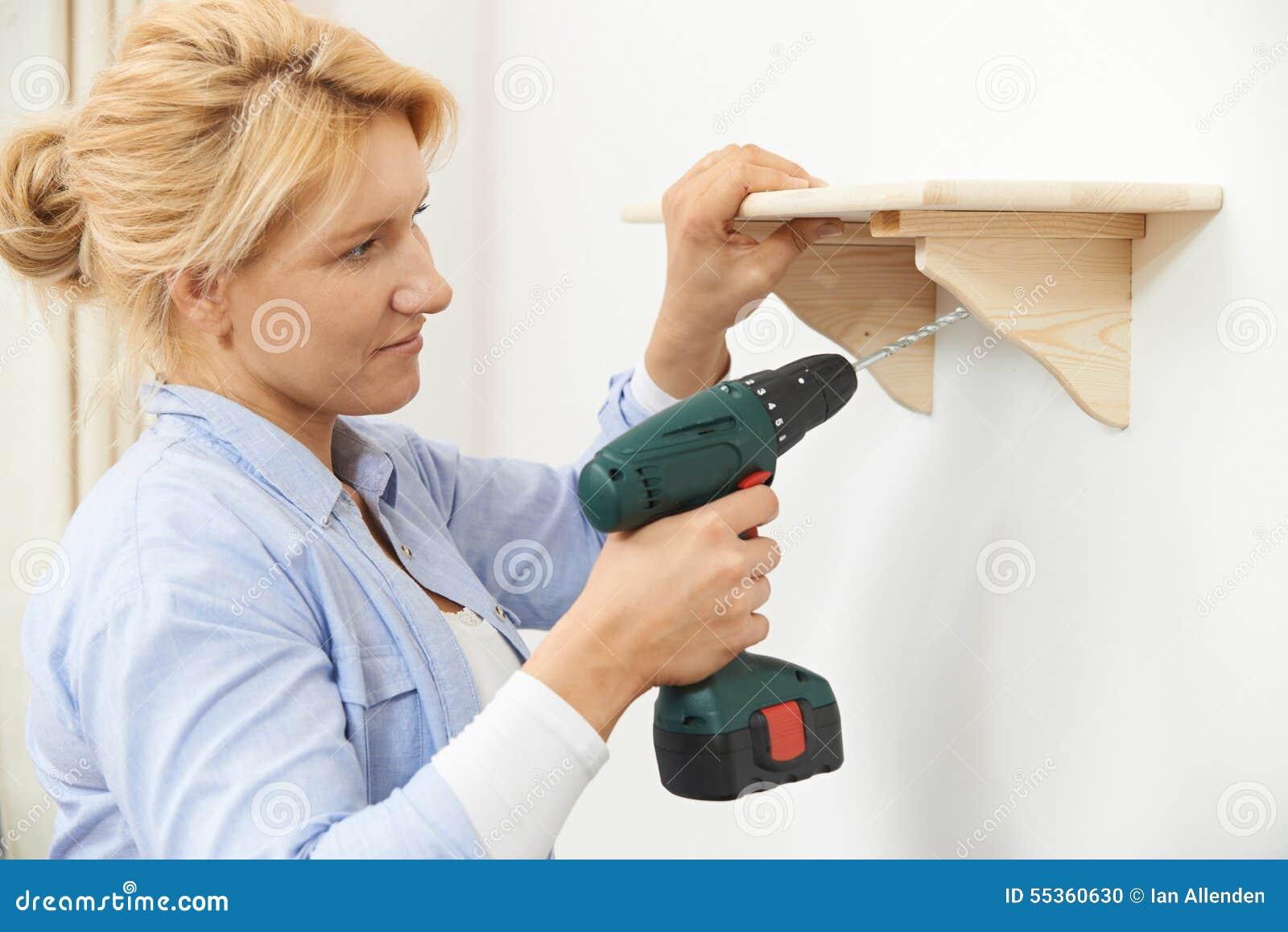 Donna che mette sullo scaffale di legno a casa facendo uso del trapano senza cordone