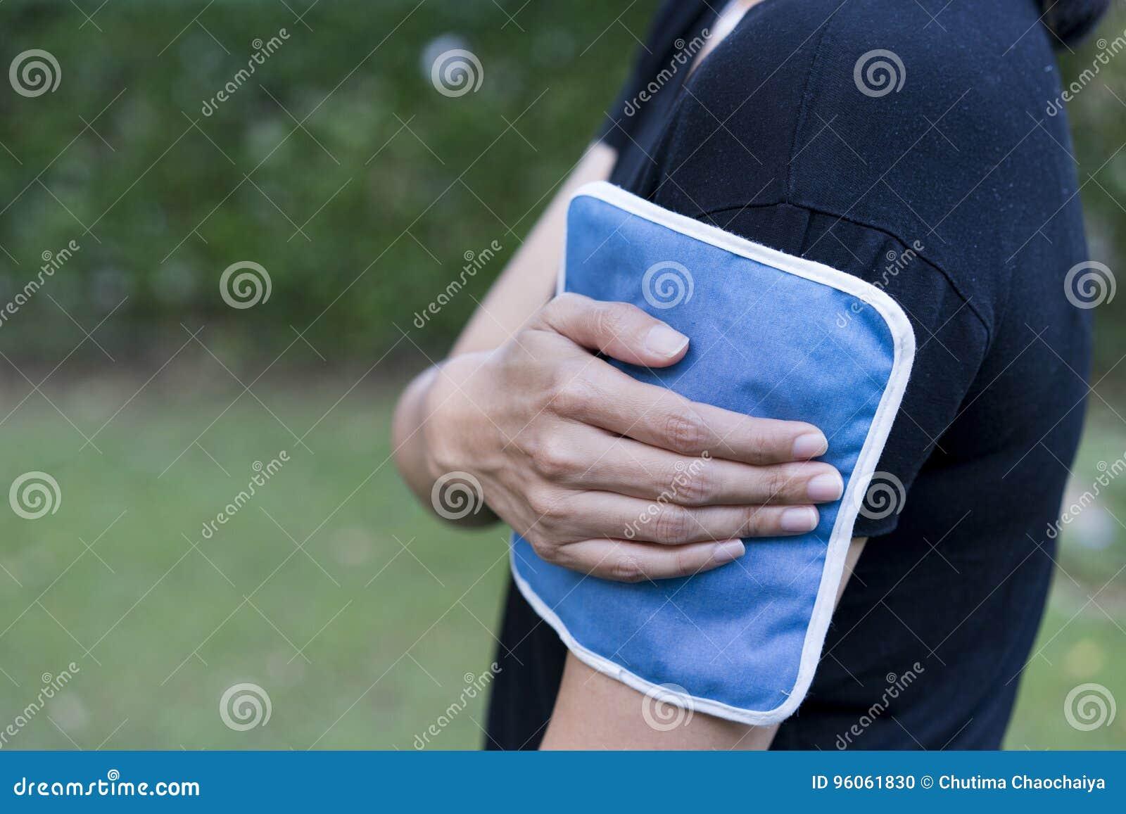 Donna che mette un pack sul suo dolore del braccio