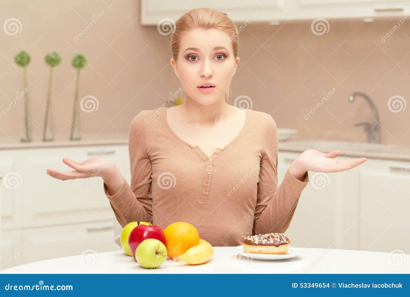Donna che opera scelta fra frutta e la ciambella