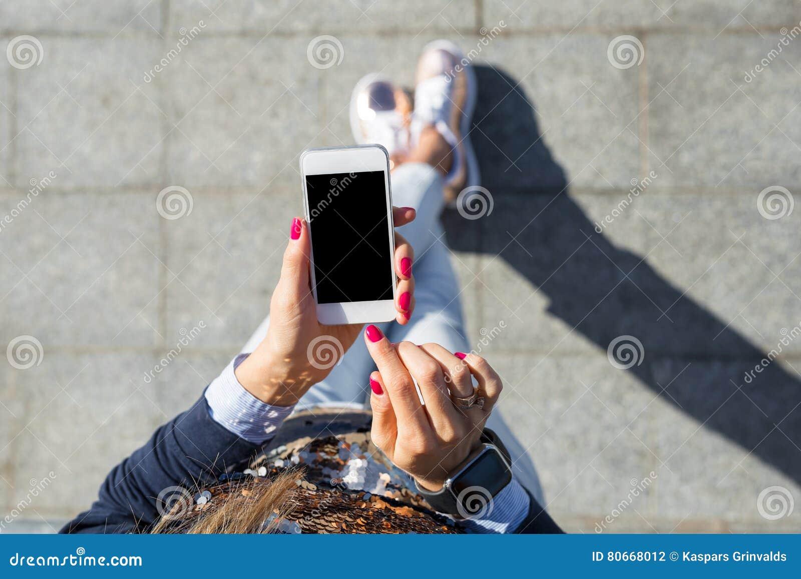 Donna che per mezzo del telefono mobile