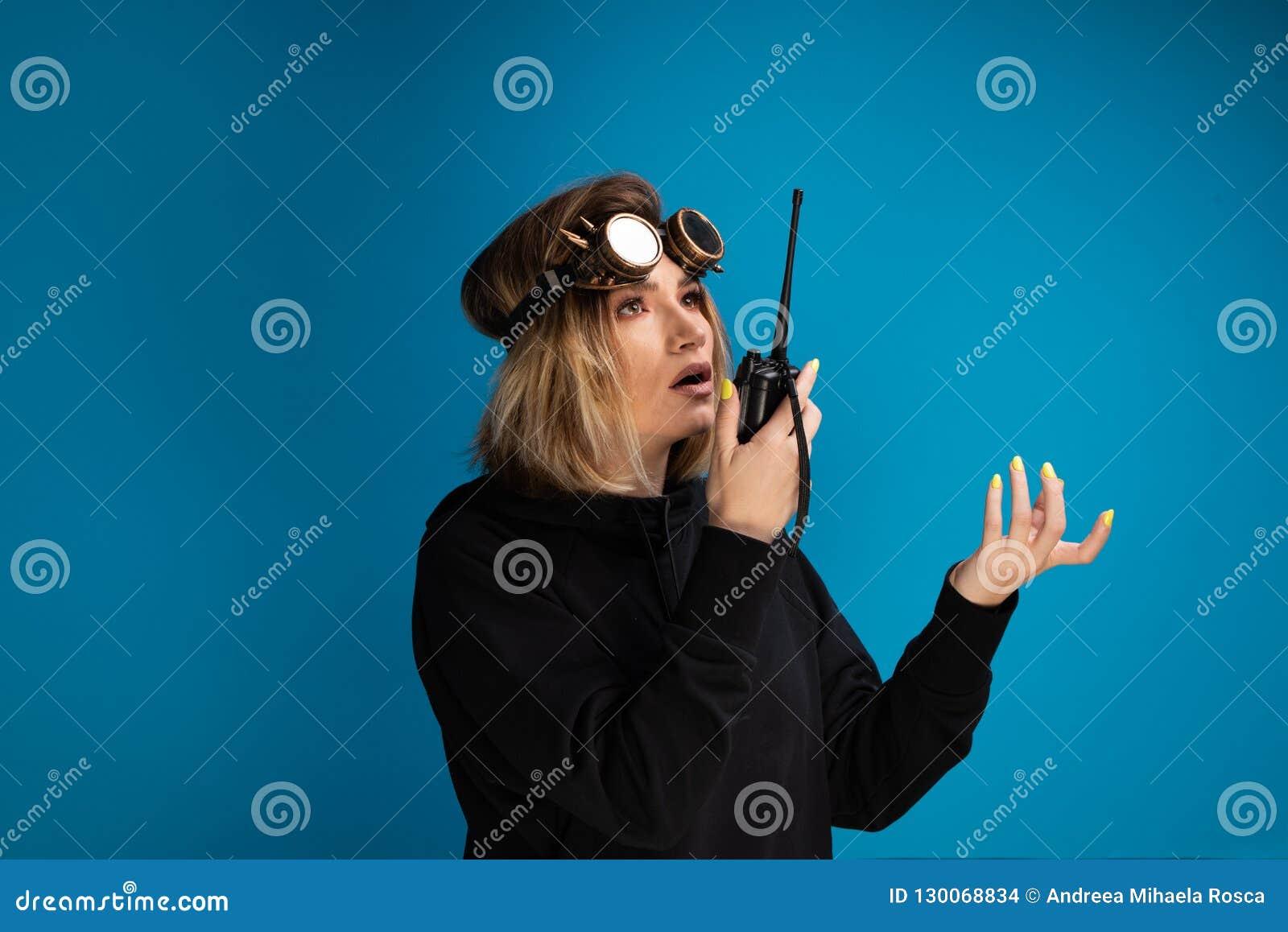 Donna che per mezzo del walkie-talkie per comunicare mentre indossando i vetri punk del vapore sulla sua testa