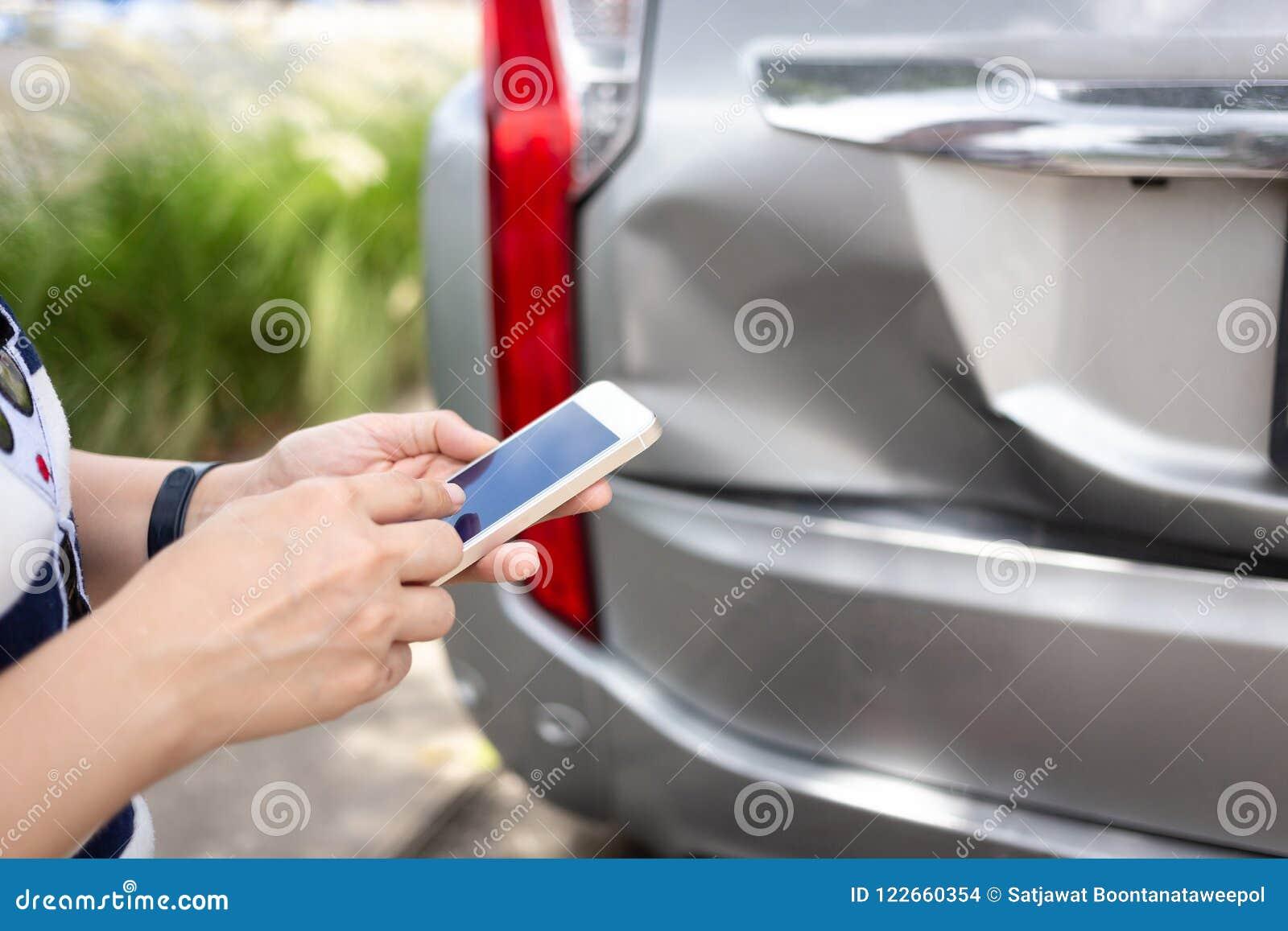 Donna che per mezzo dello smartphone al bordo della strada dopo l incidente di traffico, traffi