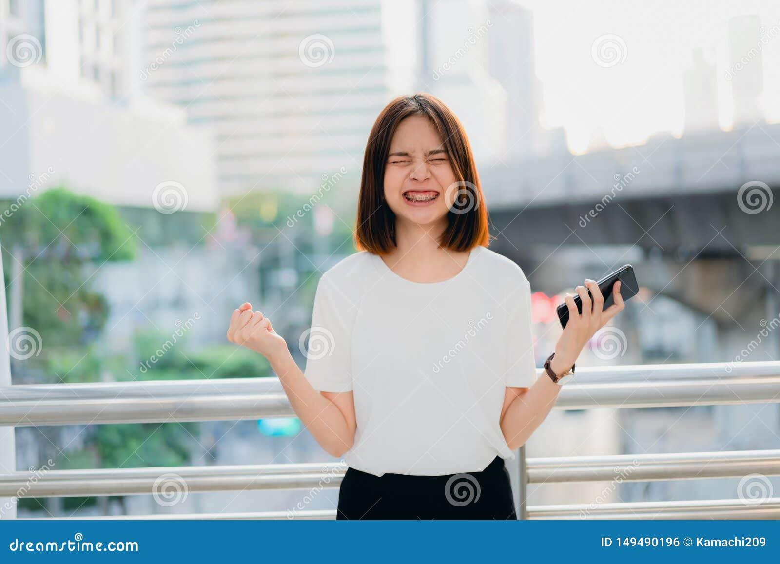 Donna che per mezzo dello smartphone, durante il tempo libero Il concetto di per mezzo del telefono