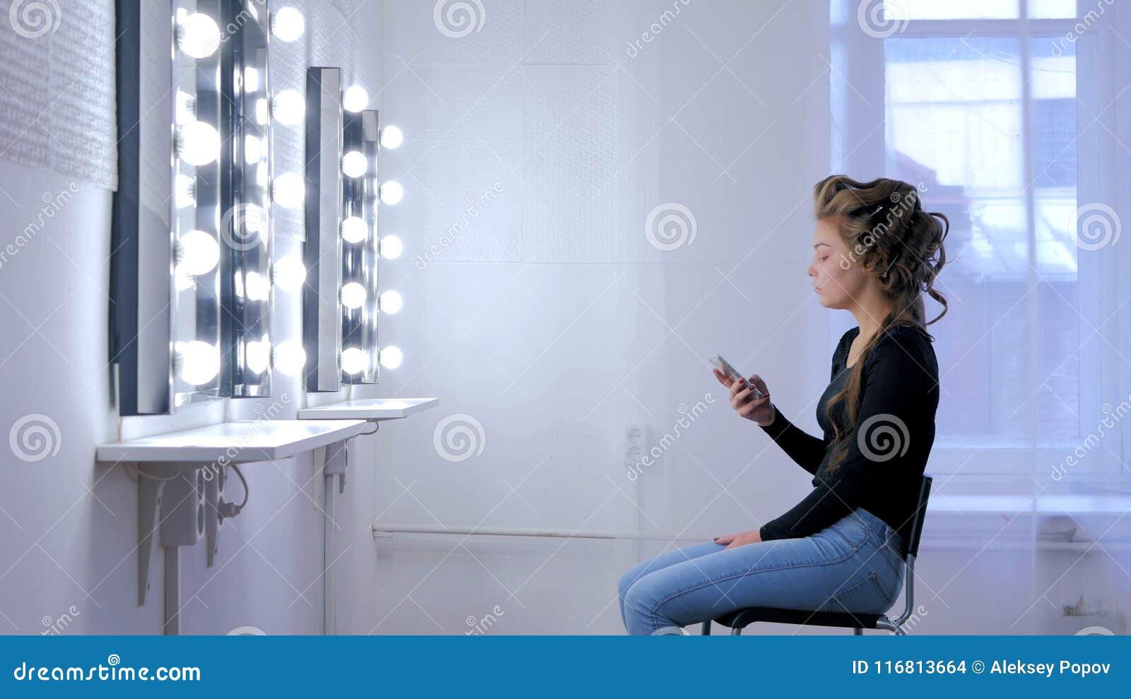 Donna che per mezzo dello smartphone che si siede davanti allo specchio