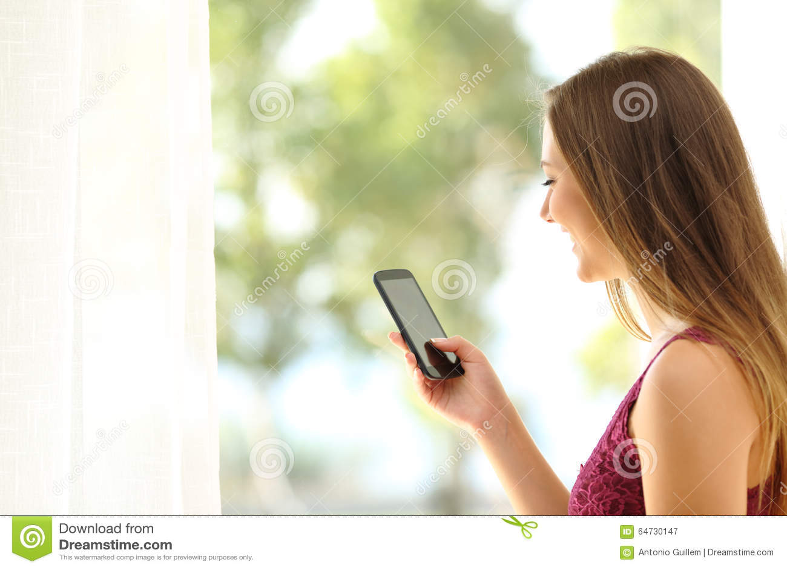 Donna che per mezzo di uno Smart Phone vicino ad una finestra