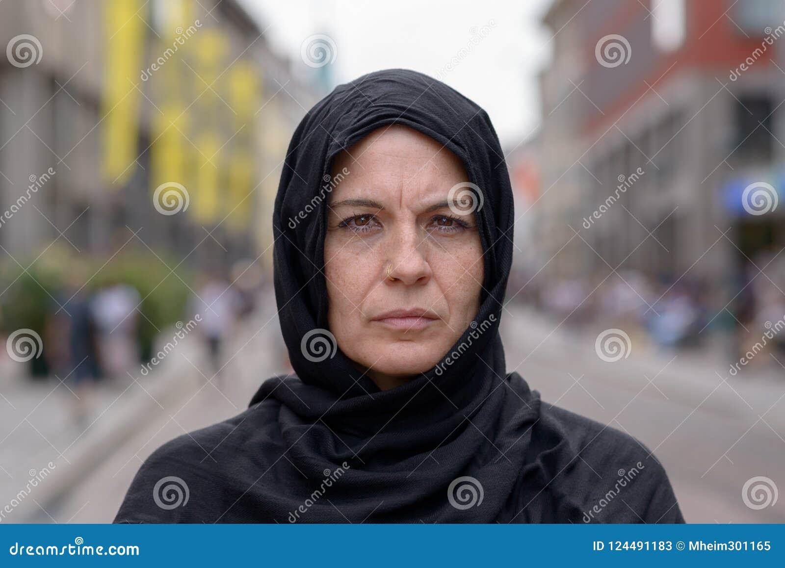 Donna che porta una sciarpa capa in una via urbana