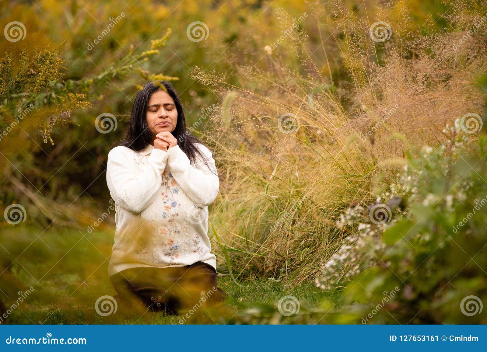 Donna che prega in Forest Preserve Alone su bello Autumn Day