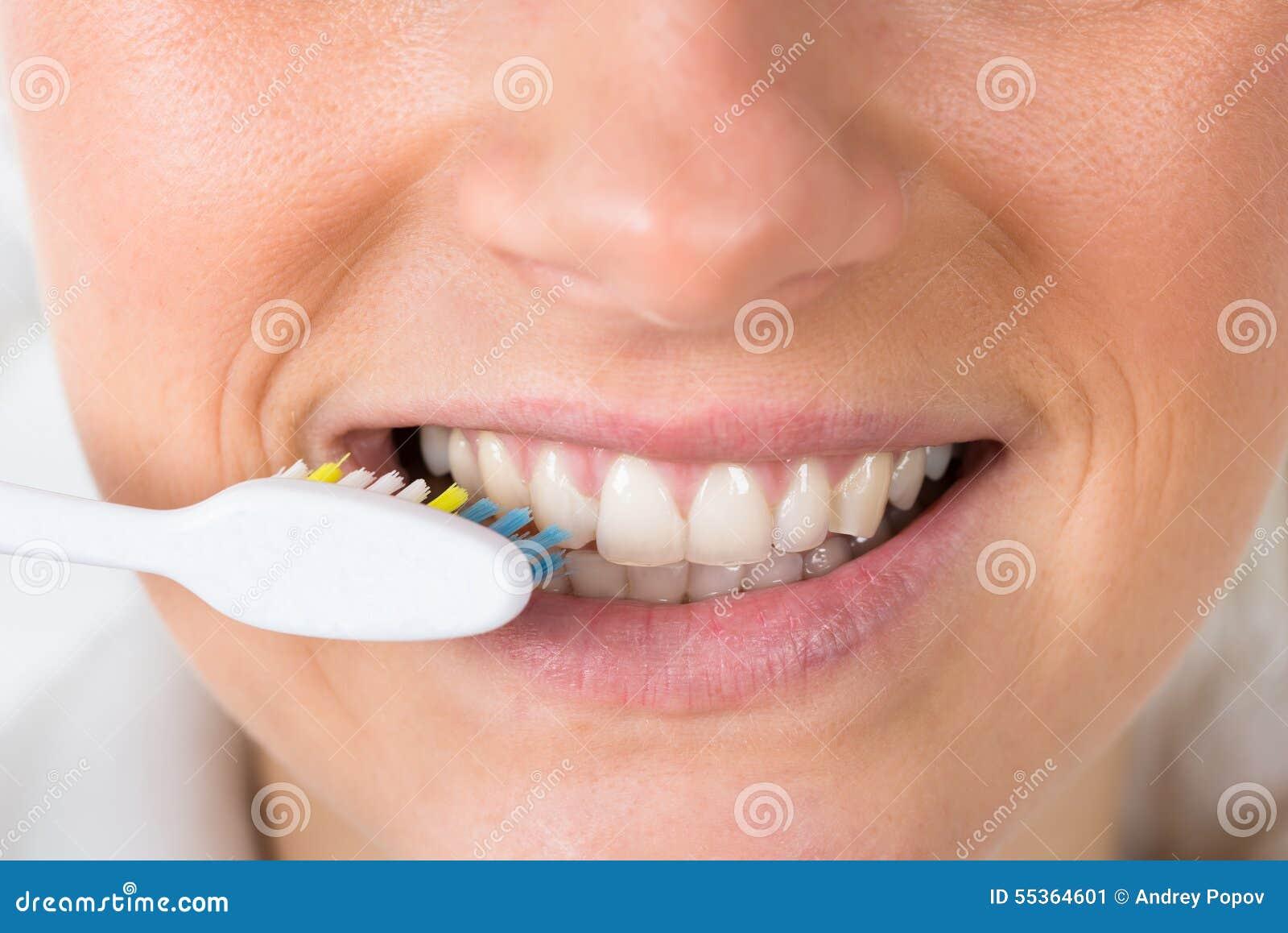 Donna che pulisce i suoi denti