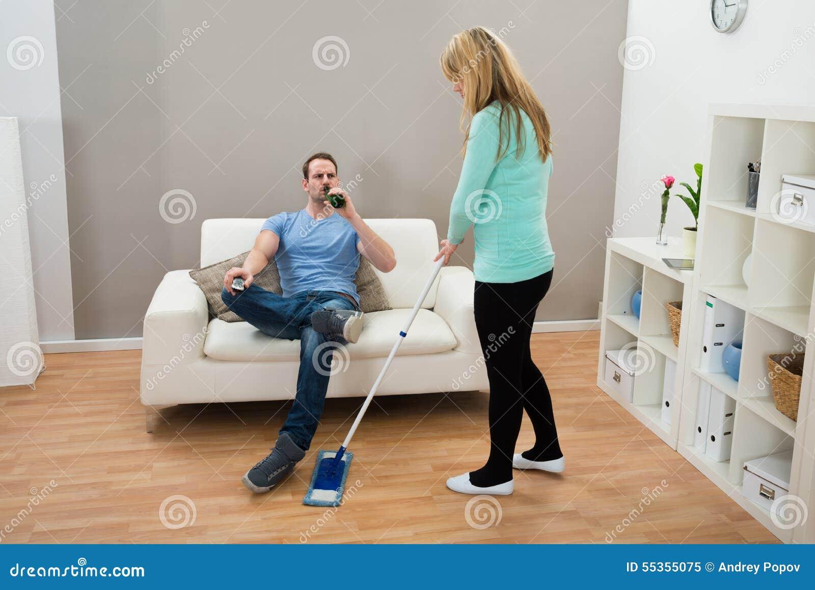 Donna che pulisce pavimento mentre alcool bevente dell uomo