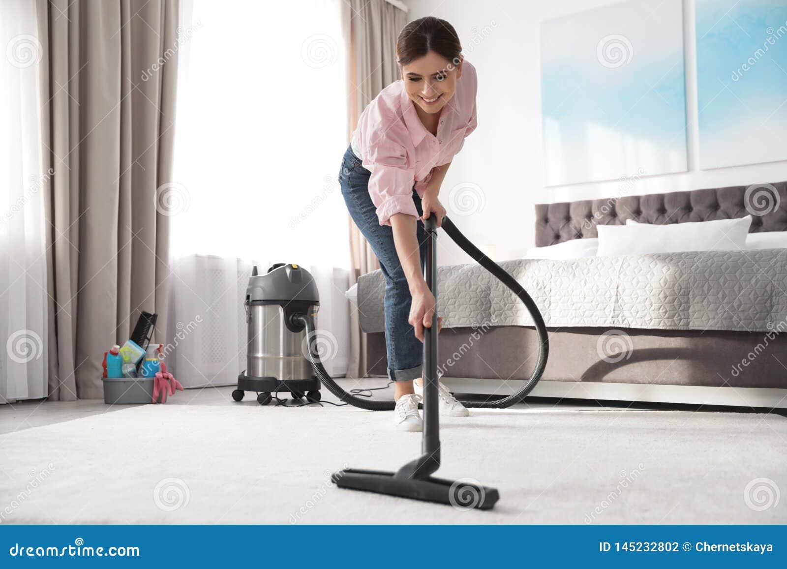 Donna che rimuove sporcizia dal tappeto con l aspirapolvere