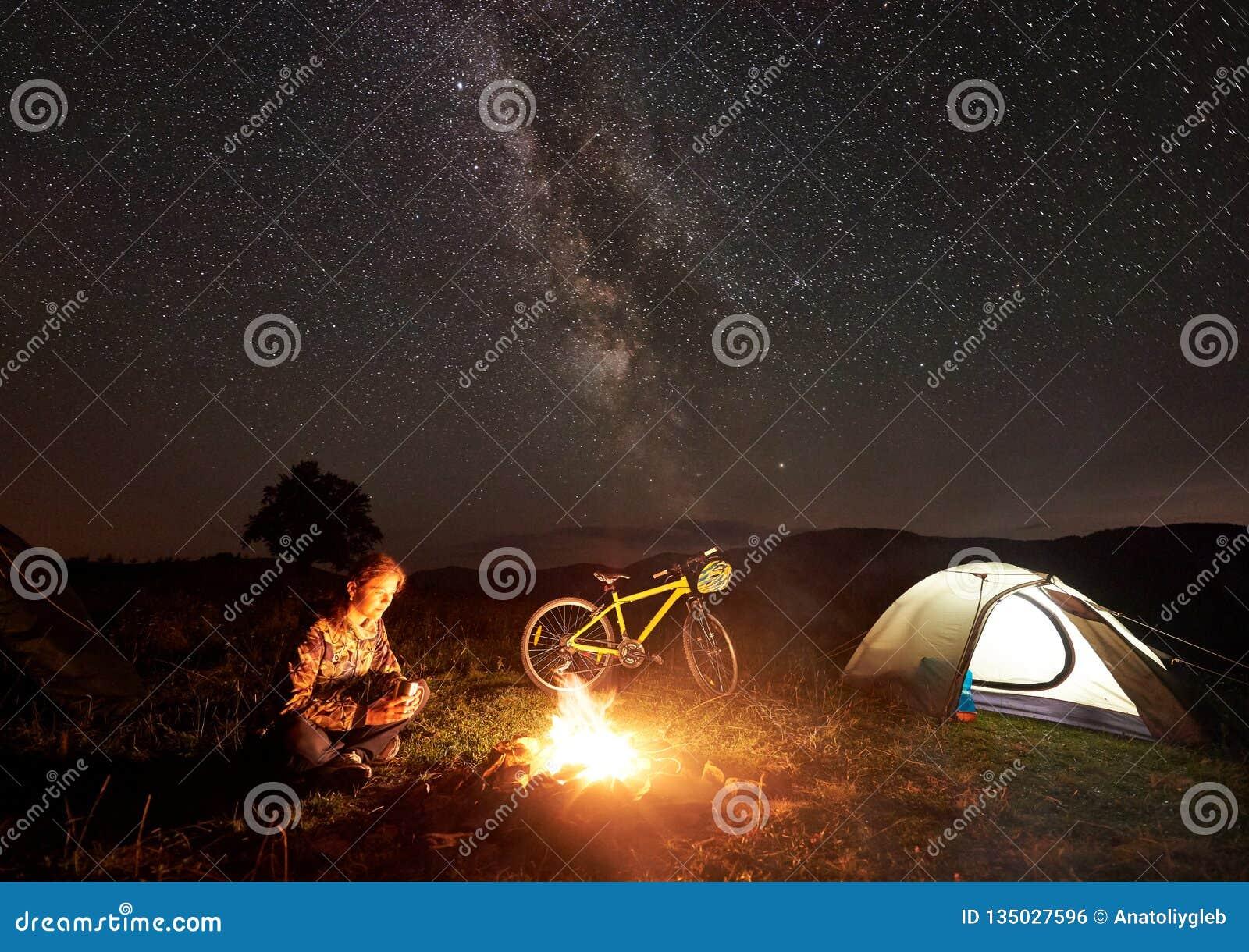 Donna che riposa alla notte che si accampa vicino al fuoco di accampamento, tenda turistica, bicicletta sotto il cielo di sera in
