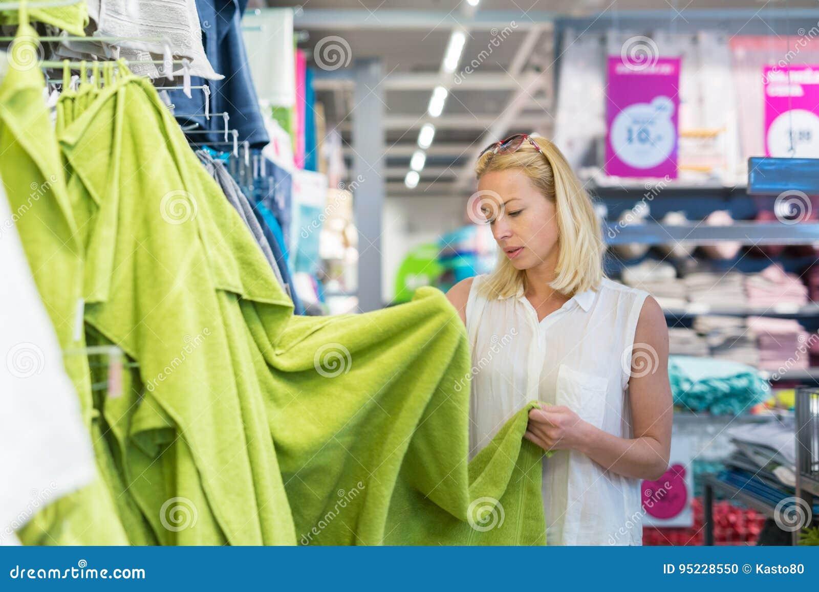 Donna che sceglie l asciugamano giusto per il suo appartamento in un deposito moderno dell arredamento domestico
