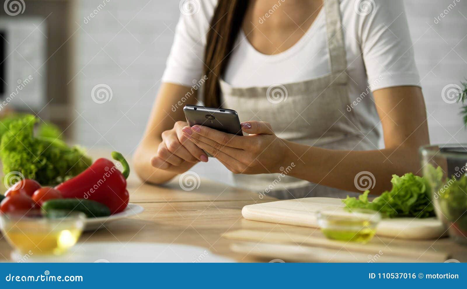 Donna che sceglie ricetta dell insalata sullo smartphone alla cucina, cucinante applicazione