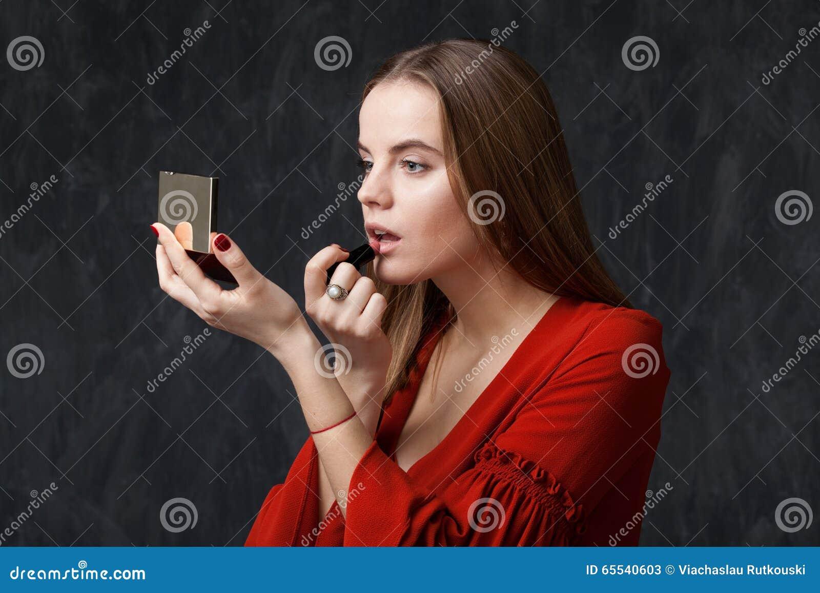 Donna che si applica rossetto che guarda dentro allo specchio fotografia stock immagine 65540603 - Bambini che si guardano allo specchio ...