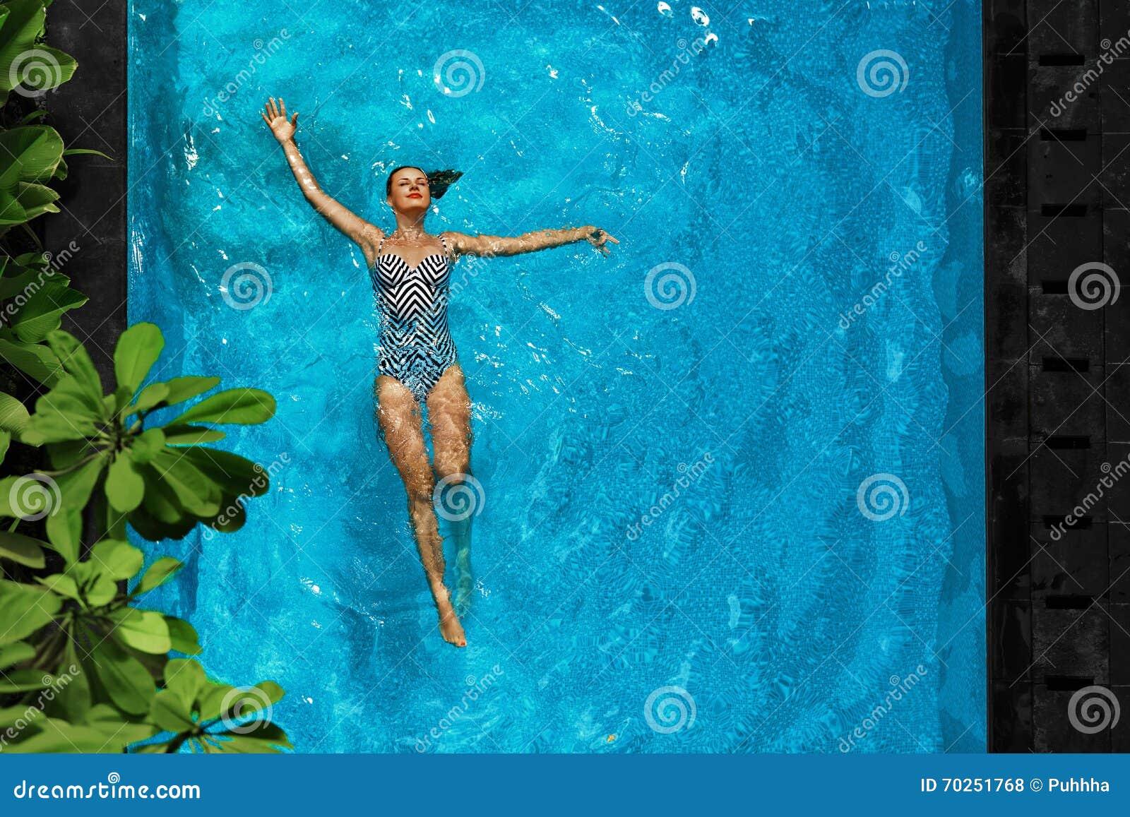 Donna che si rilassa in acqua della piscina Vacanza di vacanze estive