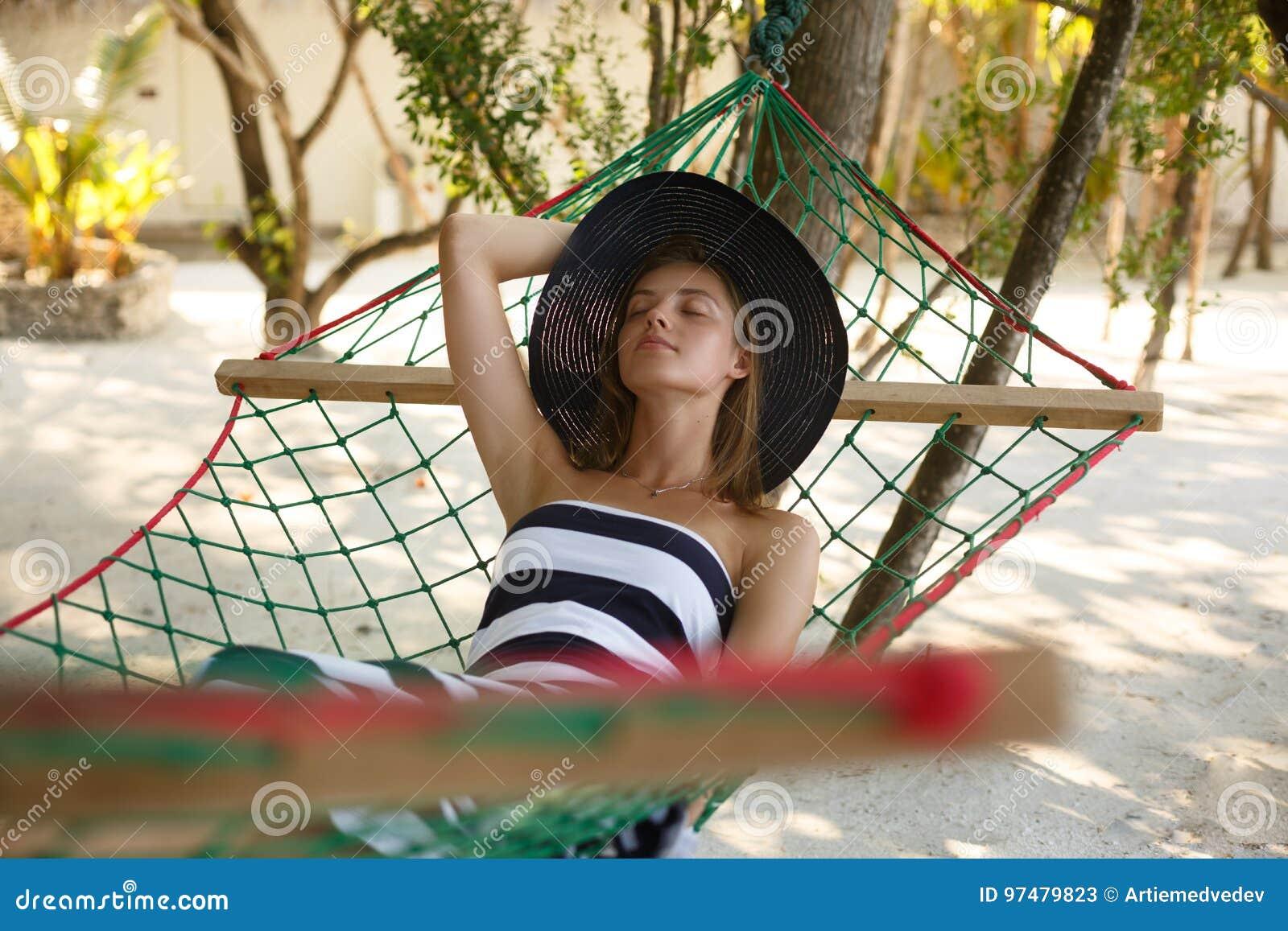 Donna che si rilassa nell amaca sulla spiaggia tropicale nell ombra, giorno soleggiato caldo