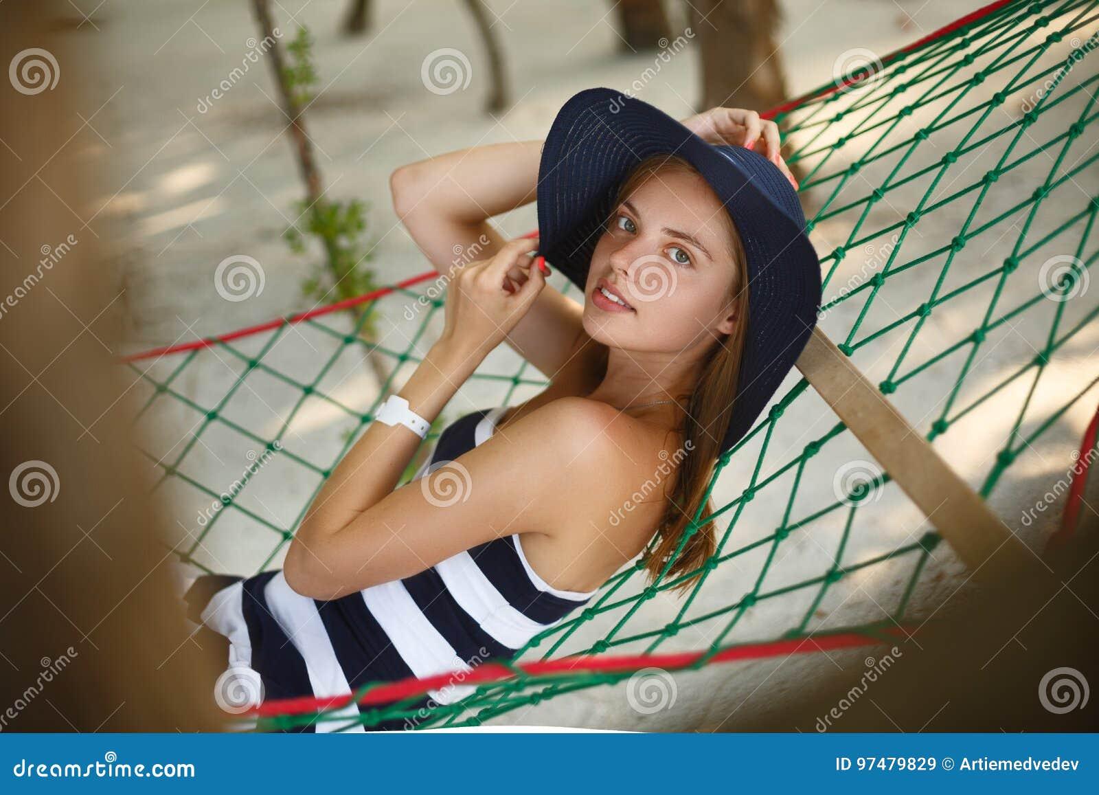 Donna che si rilassa nell amaca sulla spiaggia tropicale nell ombra, giorno soleggiato caldo La ragazza guarda alla macchina foto