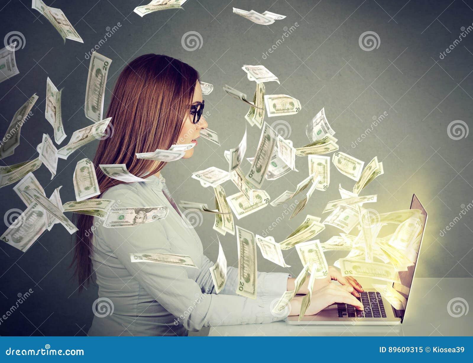 Donna che si siede alla tavola facendo uso del lavorare ad un computer portatile che fa soldi