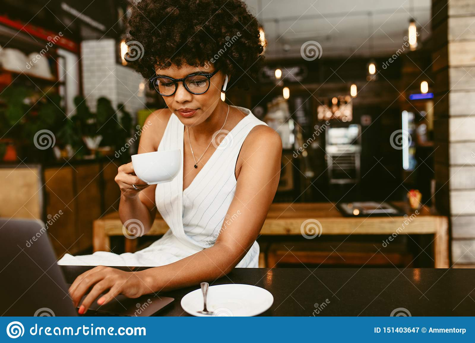 Donna che si siede in caffè con un computer portatile