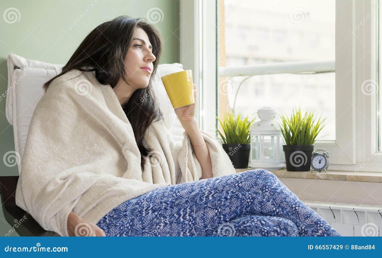 Donna che si siede a casa, avvolto in una coperta, tè bevente