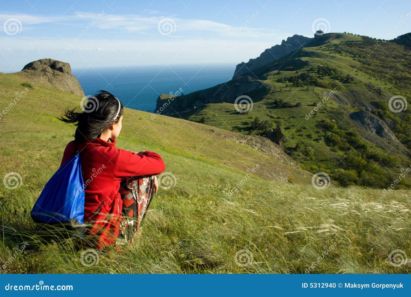 Download Donna Che Si Siede Su Una Collina E Che Osserva Al Mare Fotografia Stock - Immagine di turista, portata: 5312940