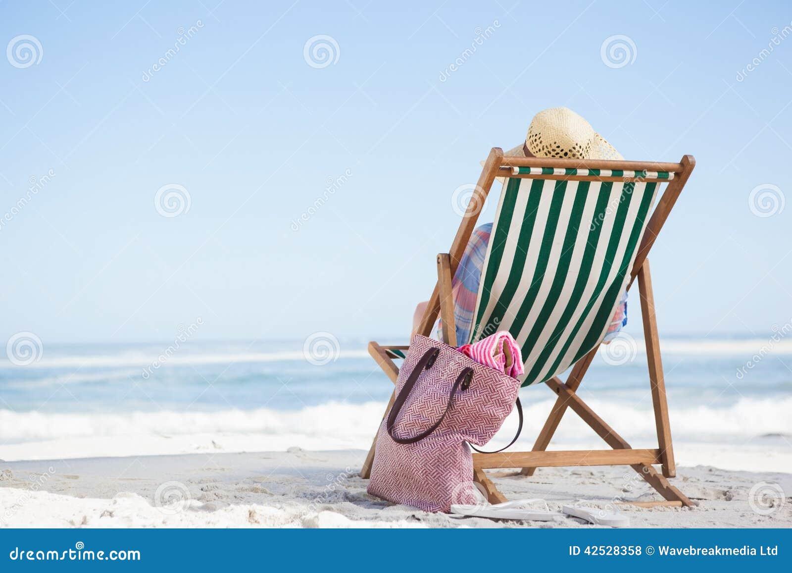 Sdraio Per La Spiaggia.Donna Che Si Siede Sulla Spiaggia Nello Sdraio Fotografia Stock