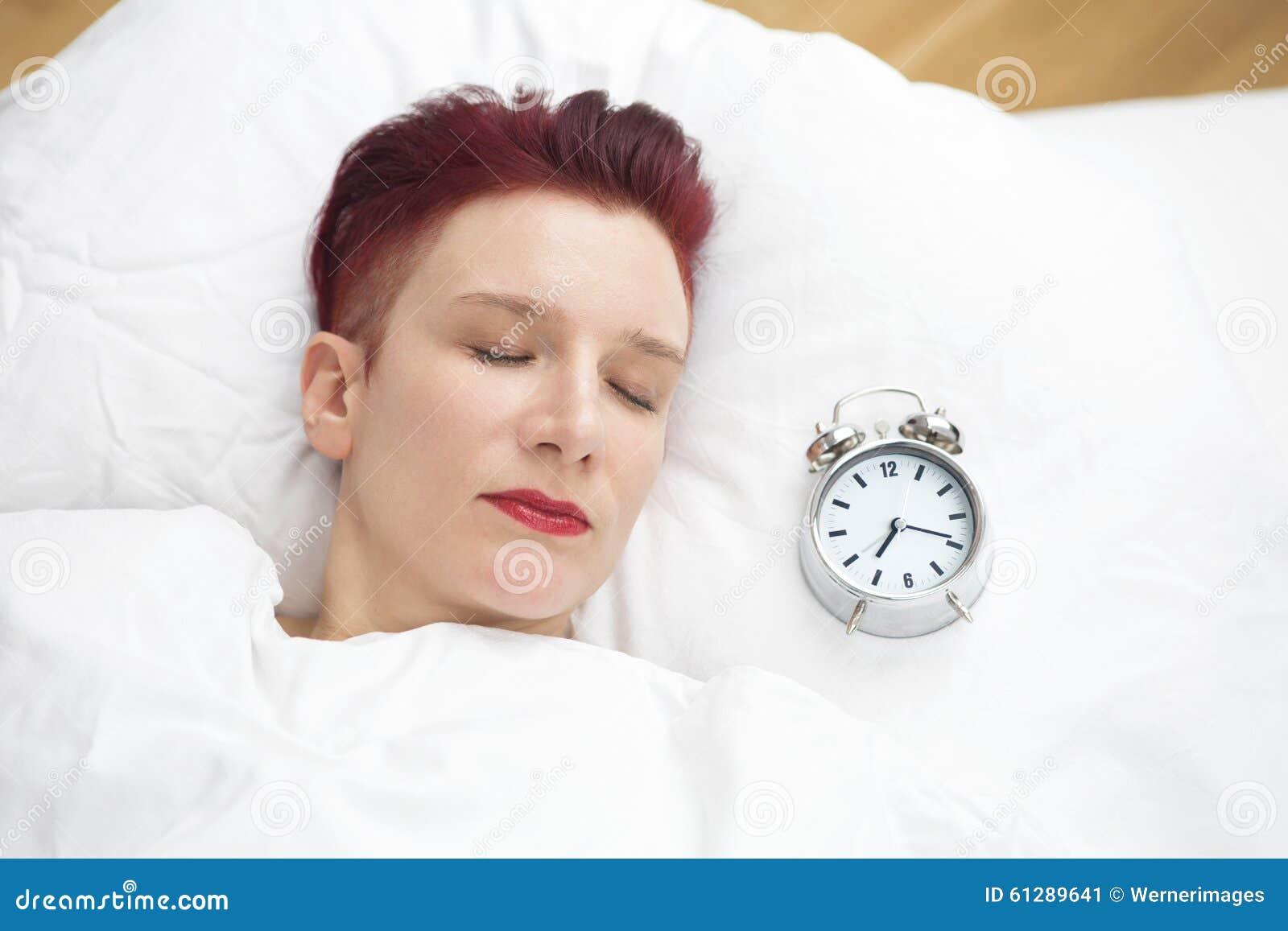 Donna che si trova a letto con la sveglia sul cuscino immagine stock immagine di interno - Letto che si chiude ...
