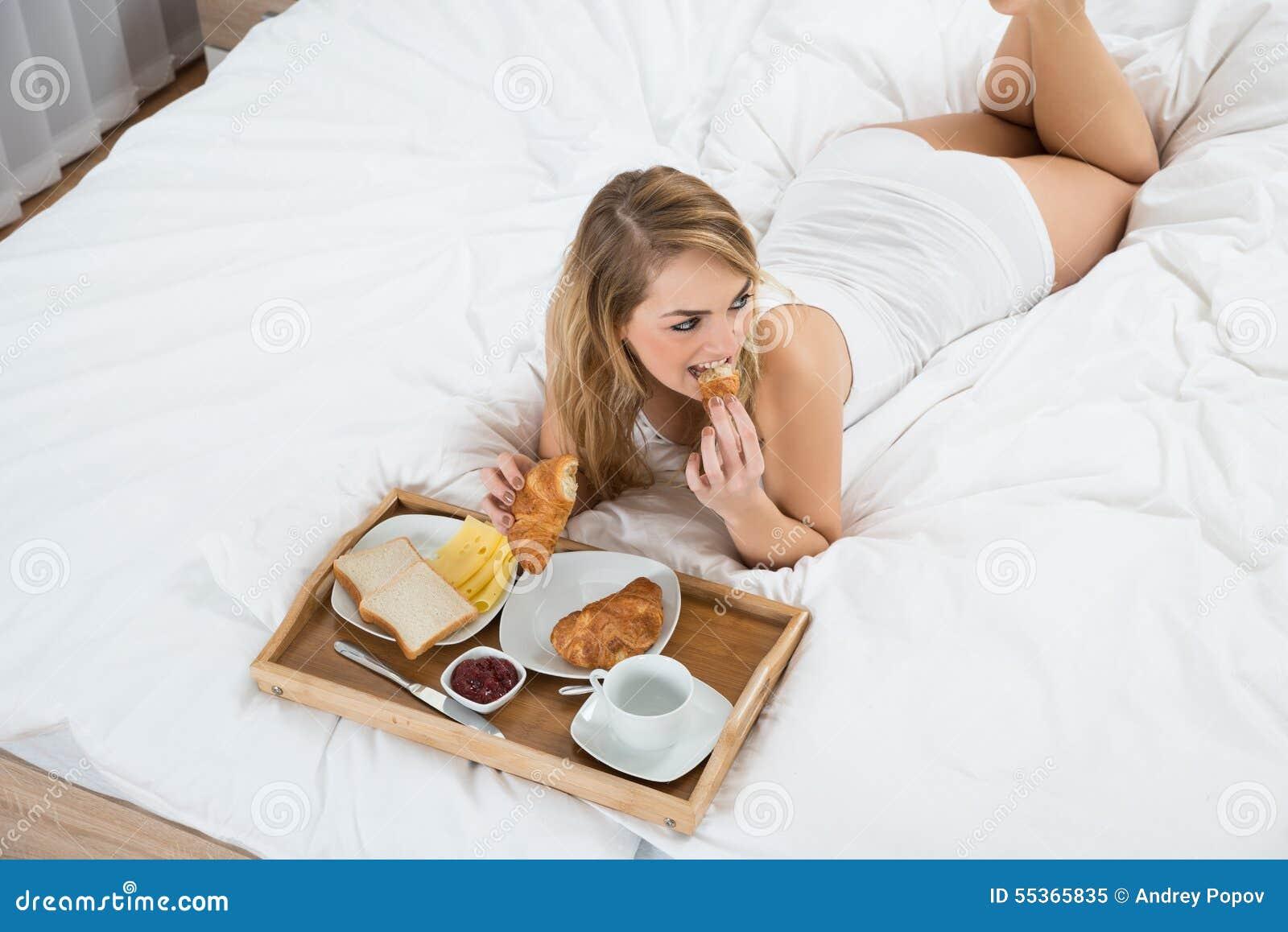 Donna che si trova sul letto che mangia prima colazione