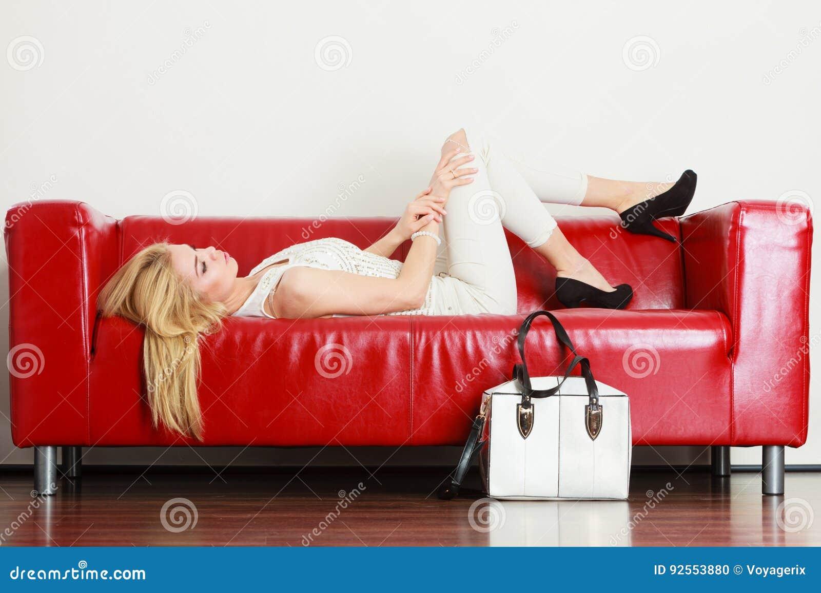 Donna che si trova sul sofà che presenta borsa bianca