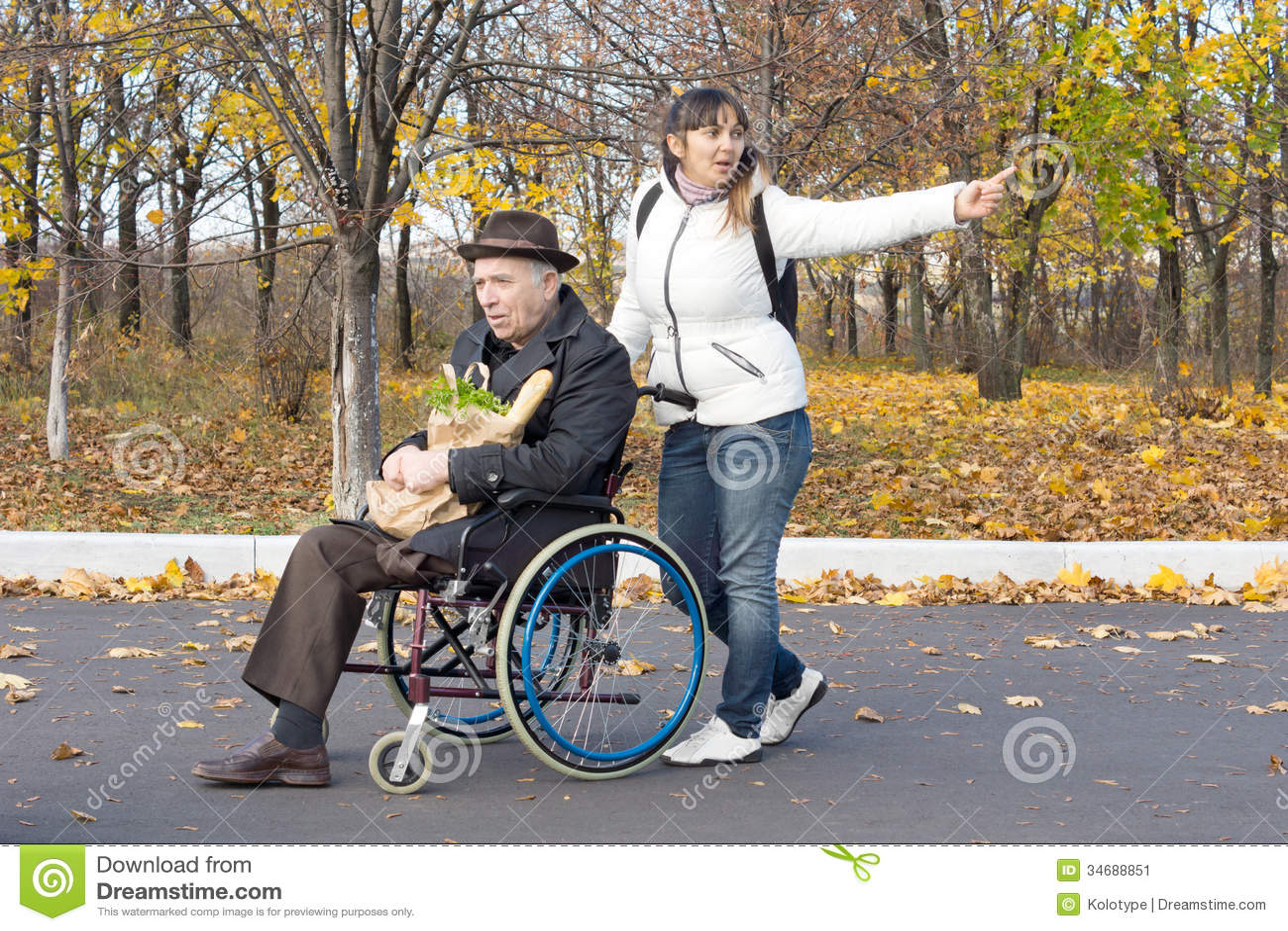 donna che spinge un uomo anziano in una sedia a rotelle