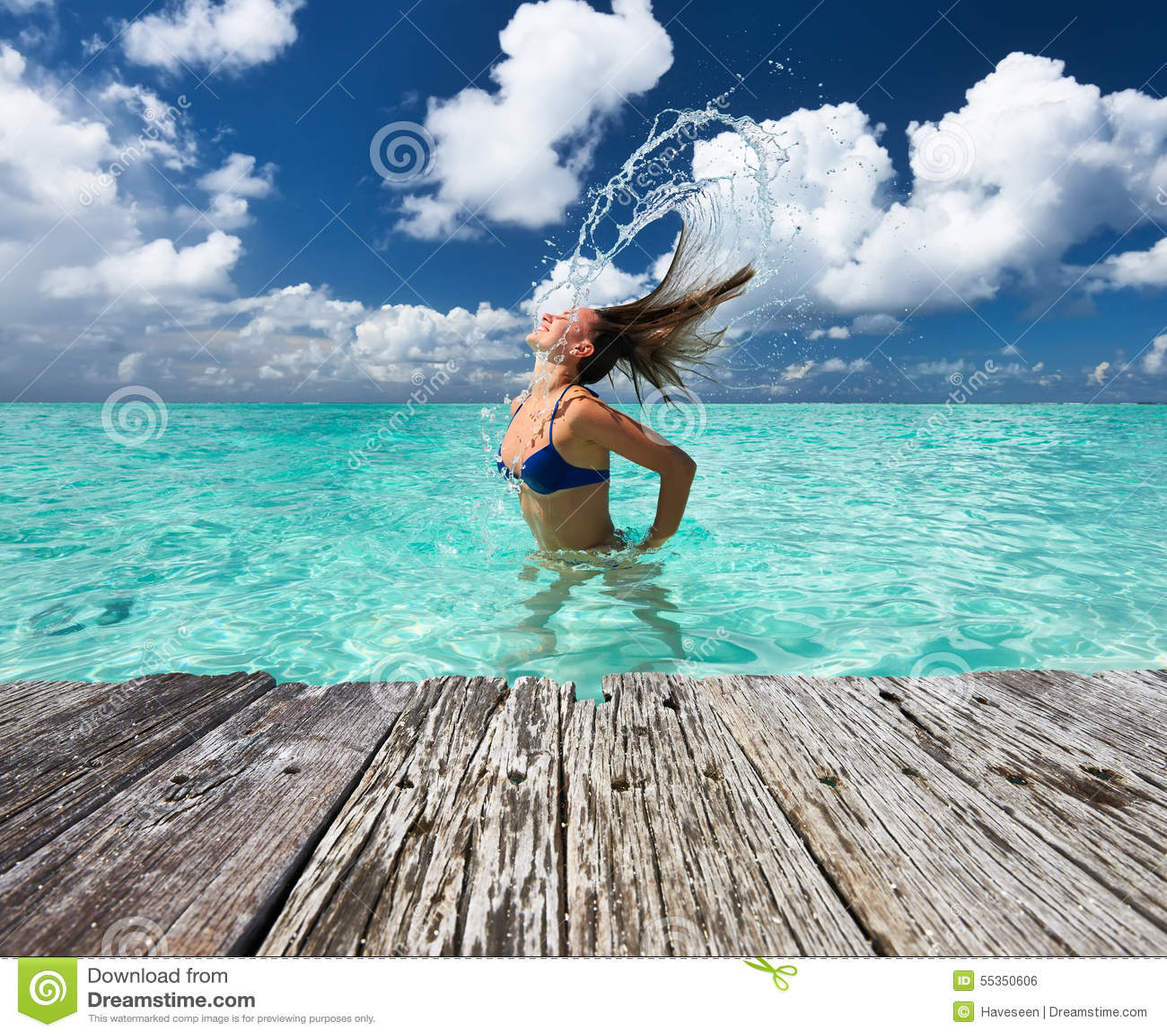 Donna che spruzza acqua con i capelli nell oceano