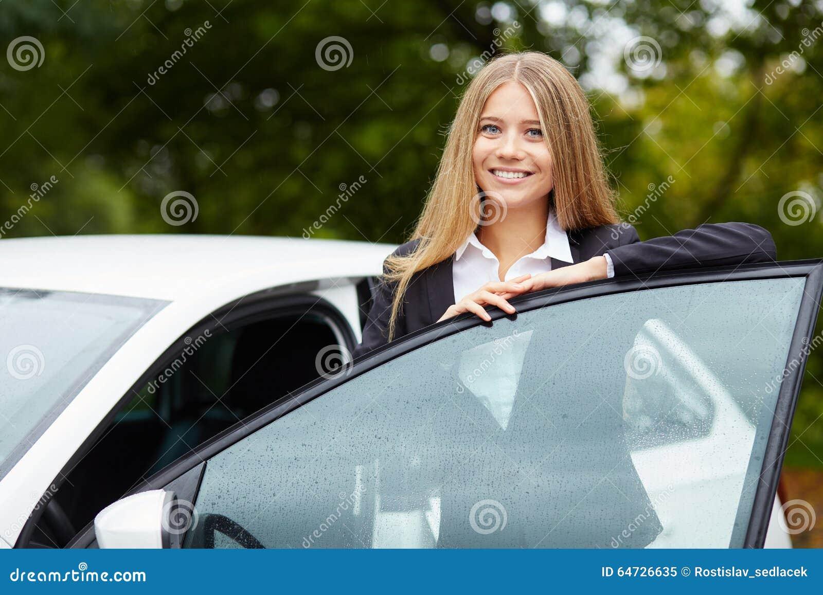 Donna che sta e che si appoggia la porta di automobile