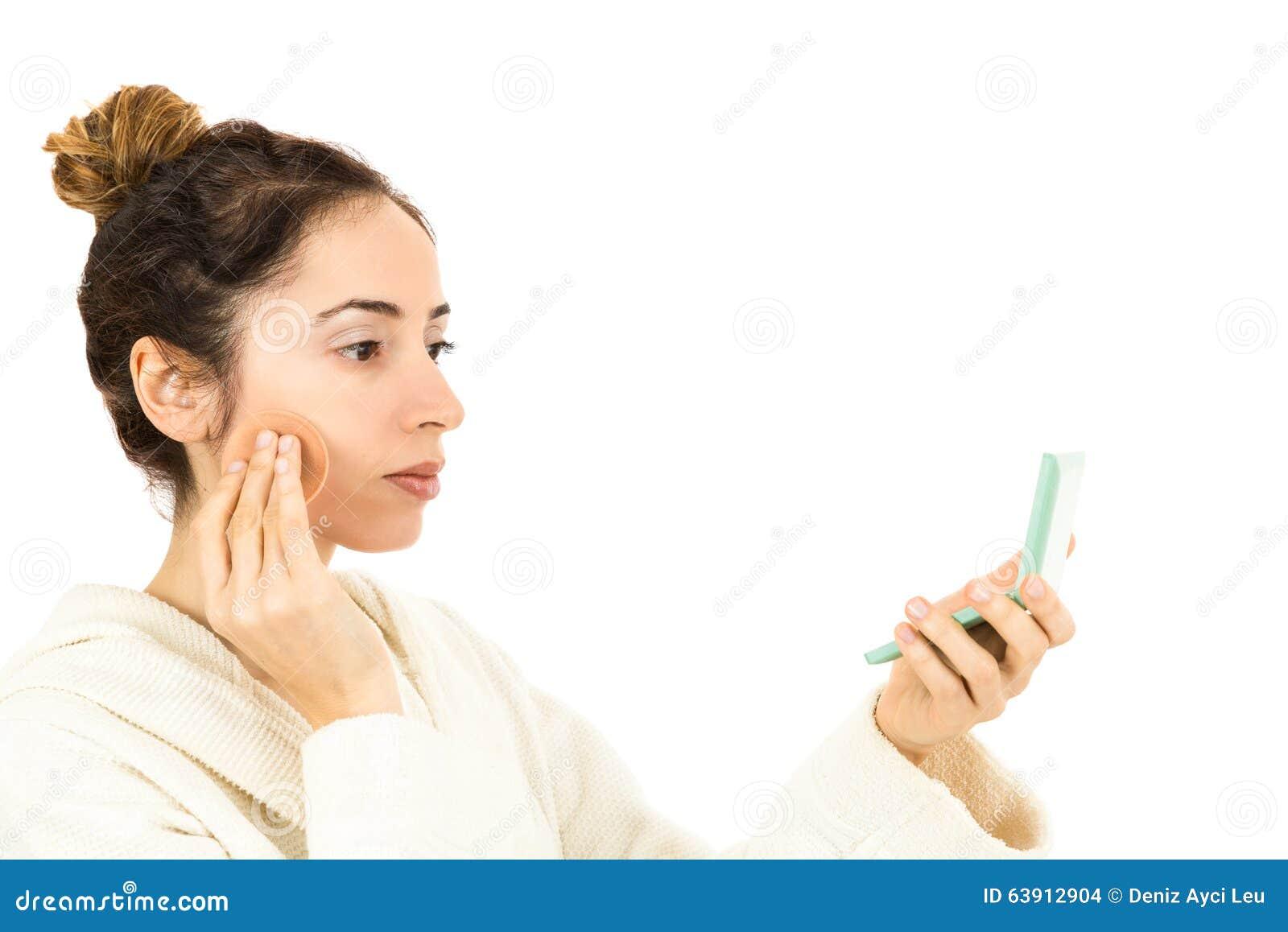 Donna che stende il trucco guardando su suo specchio