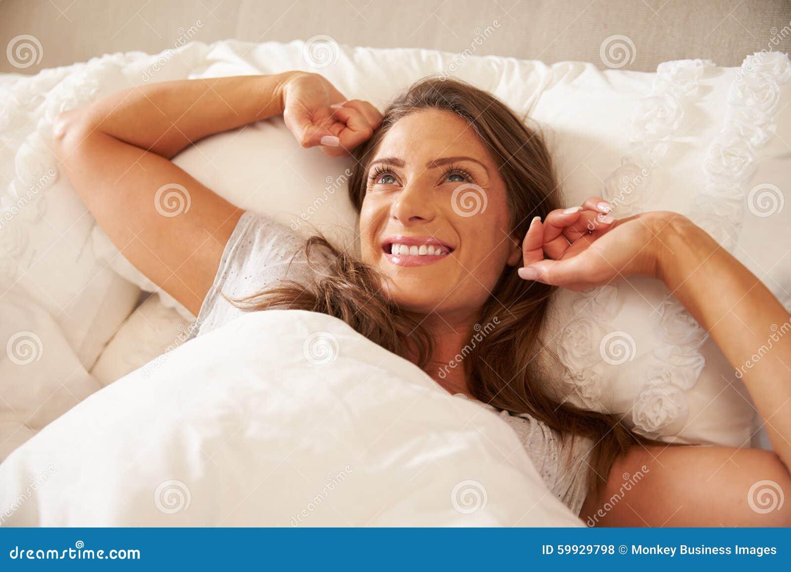 Donna che sveglia e che allunga a letto a casa