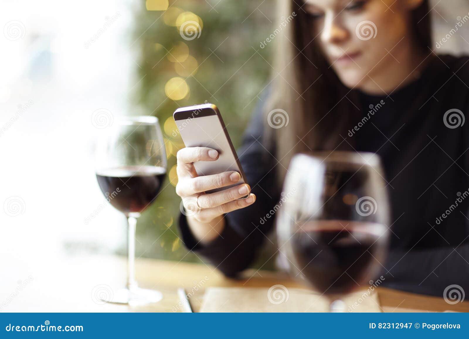 ecdbd6664fc7ab Donna che per mezzo del telefono durante il pranzo Bicchiere di vino rosso  in un caffè Riunione degli amici dell'interno Busta di carta dei pantaloni  a vita ...